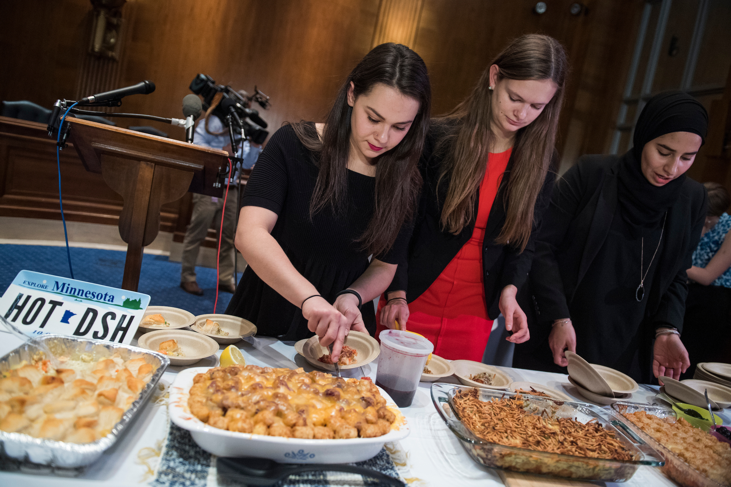 Aides to Sen. Al Franken, D-Minn., from left, Naomi Sibel, Erin Carvers, and Ayah Housini, serve food during the annual Minnesota Congressional Delegation Hotdish Competition in Dirksen Building on Wednesday. (Tom Williams/CQ Roll Call)