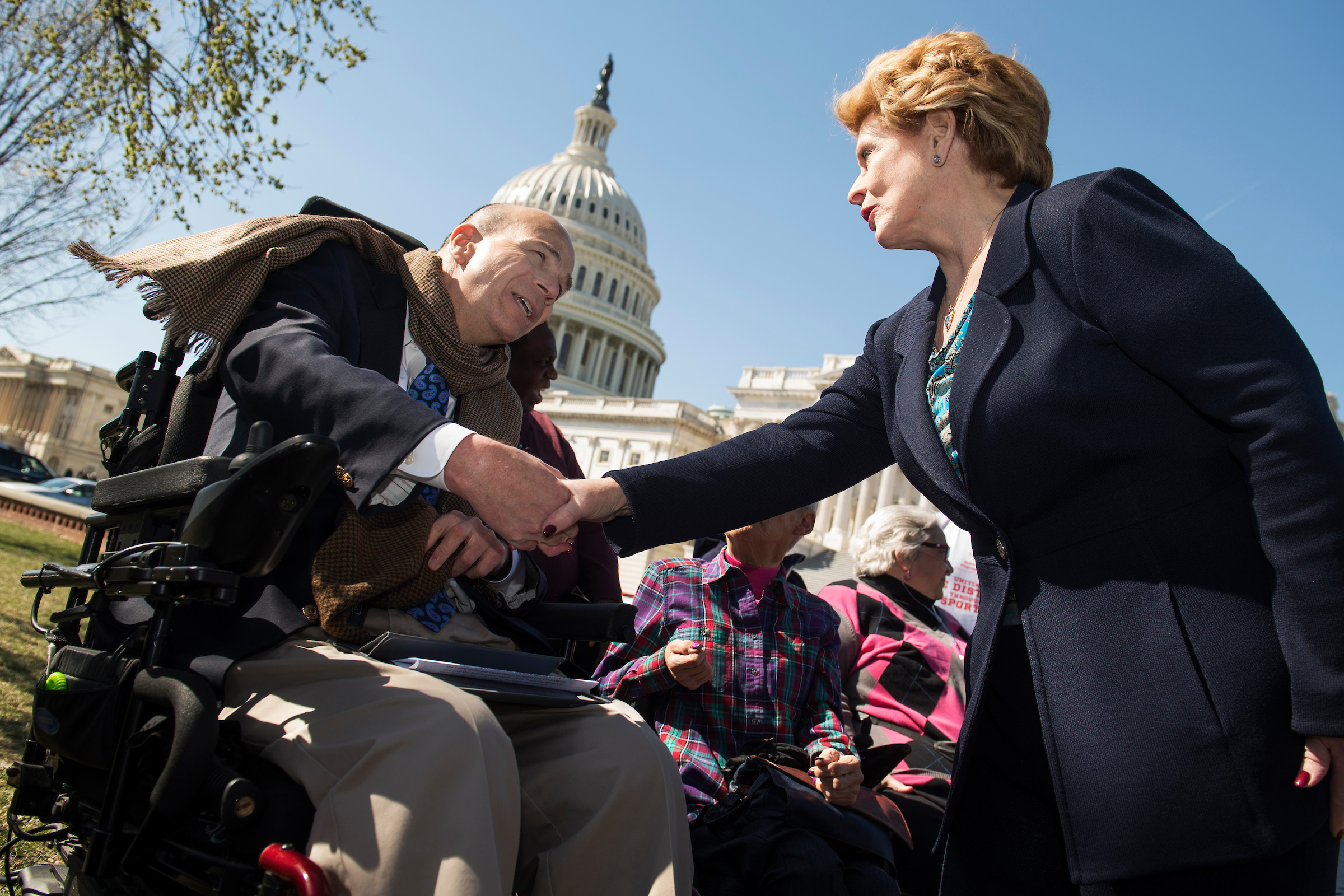 Sen. Debbie Stabenow, D-Mich., greets Kent Keyser of the United Spinal Association, during a news conference to defend the Affordable Care Act on Thursday. (Tom Williams/CQ Roll Call)
