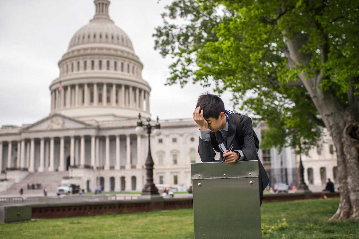 APRIL 26: A student from Wisconsin takes a break on the East Front of the Capitol. (Tom Williams/CQ Roll Call)