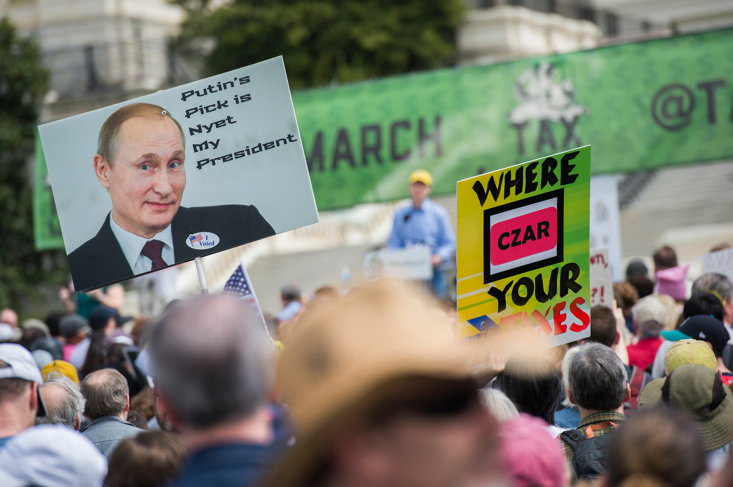 UNITED STATES - APRIL 15: People gather for the Tax March rally on the west lawn of the Capitol to call on President Trump to release his tax returns, April 15, 2017. Sen. Ron Wyden, D-Ore., speaks on stage. (Photo By Tom Williams/CQ Roll Call)