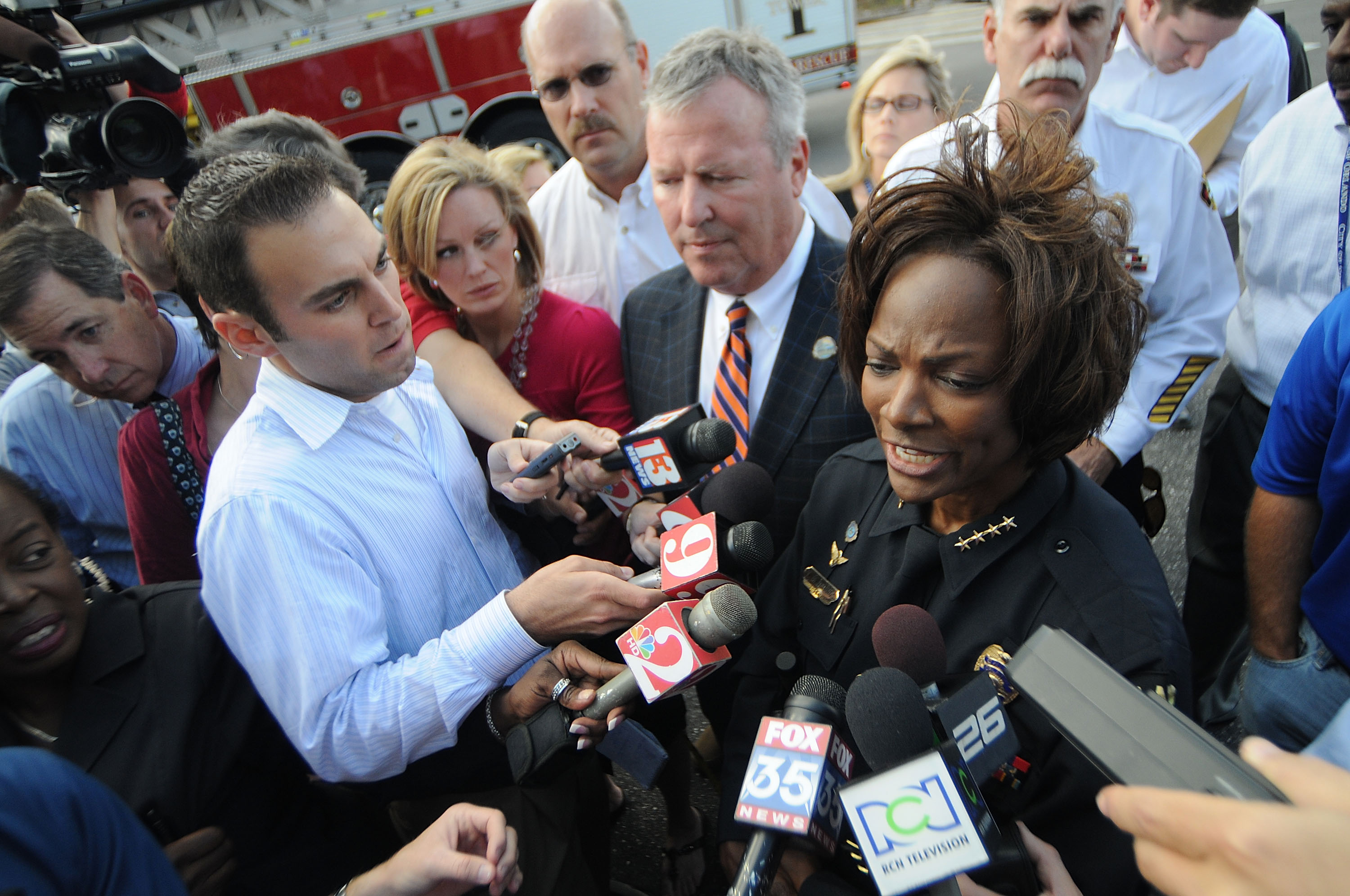 Demings, as Orlando police chief, speaks to reporters with Orlando Mayor Buddy Dyer, center, near the site of an office building where a gunman opened fire, killing one person and wounding several others, in 2009. (Gerardo Mora/Getty Images file photo)