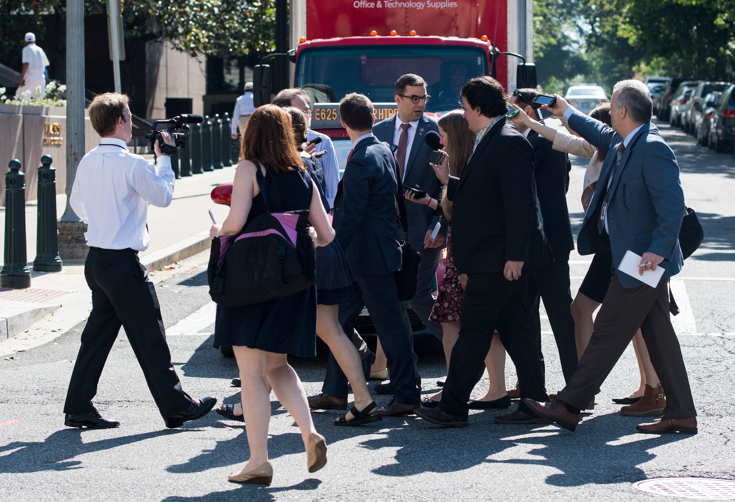 Reporters follow Rep. Justin Amash, R-Mich., across the street as he leaves the House Republican Conference meeting at the Capitol Hill Club in Washington on Wednesday. (Bill Clark/CQ Roll Call)