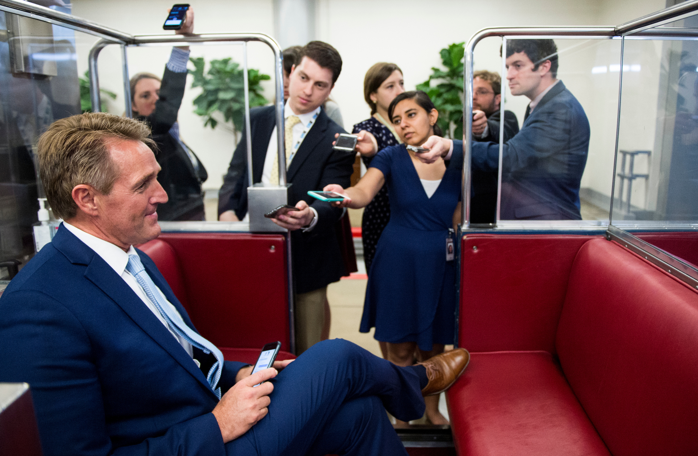 Arizona Sen. Jeff Flake talks with reporters as he rides the Senate subway to the Russell Senate Office Building on Tuesday. (Bill Clark/CQ Roll Call)