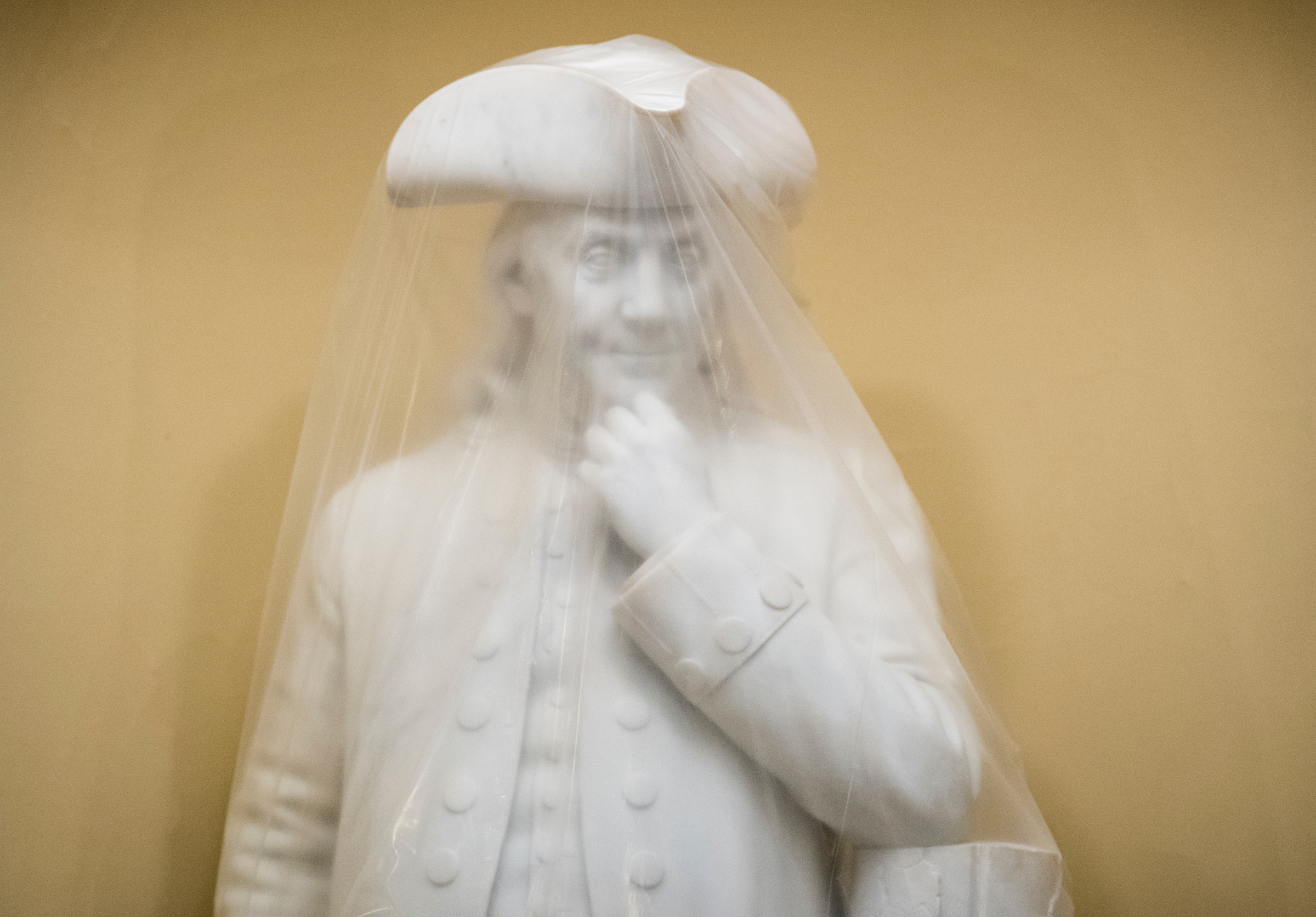 A plastic sheet covers the statue of Ben Franklin in the Capitol on Wednesday. (Bill Clark/CQ Roll Call)