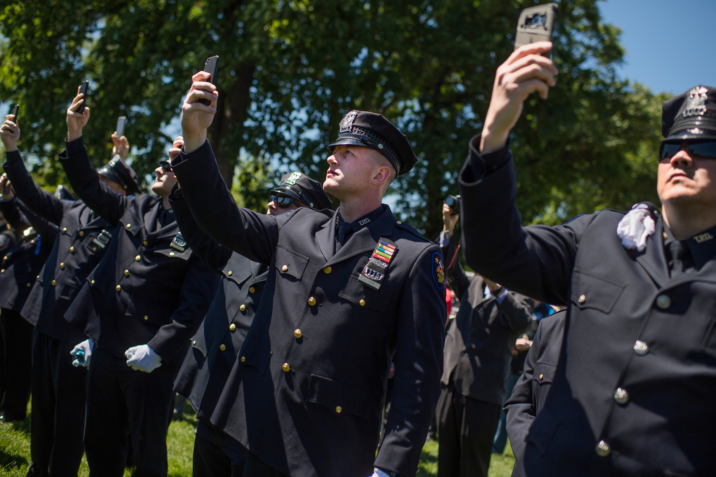 UNITED STATES - MAY 15: Off. Jarrod Iler of the Troy, N.Y., Police takes a picture of President Donald Trump addressing the 36h Annual National Peace Officers' Memorial Service on the West Front lawn of the Capitol on May 15, 2017. (Photo By Tom Williams/CQ Roll Call)