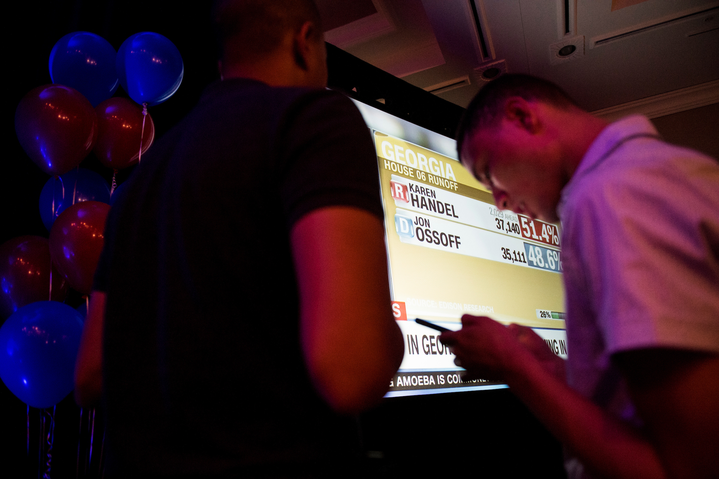 Supporters of Democrat Jon Ossoff check their phones for early results at Ossoff's election night watch party in Atlanta on Tuesday. (Bill Clark/CQ Roll Call)