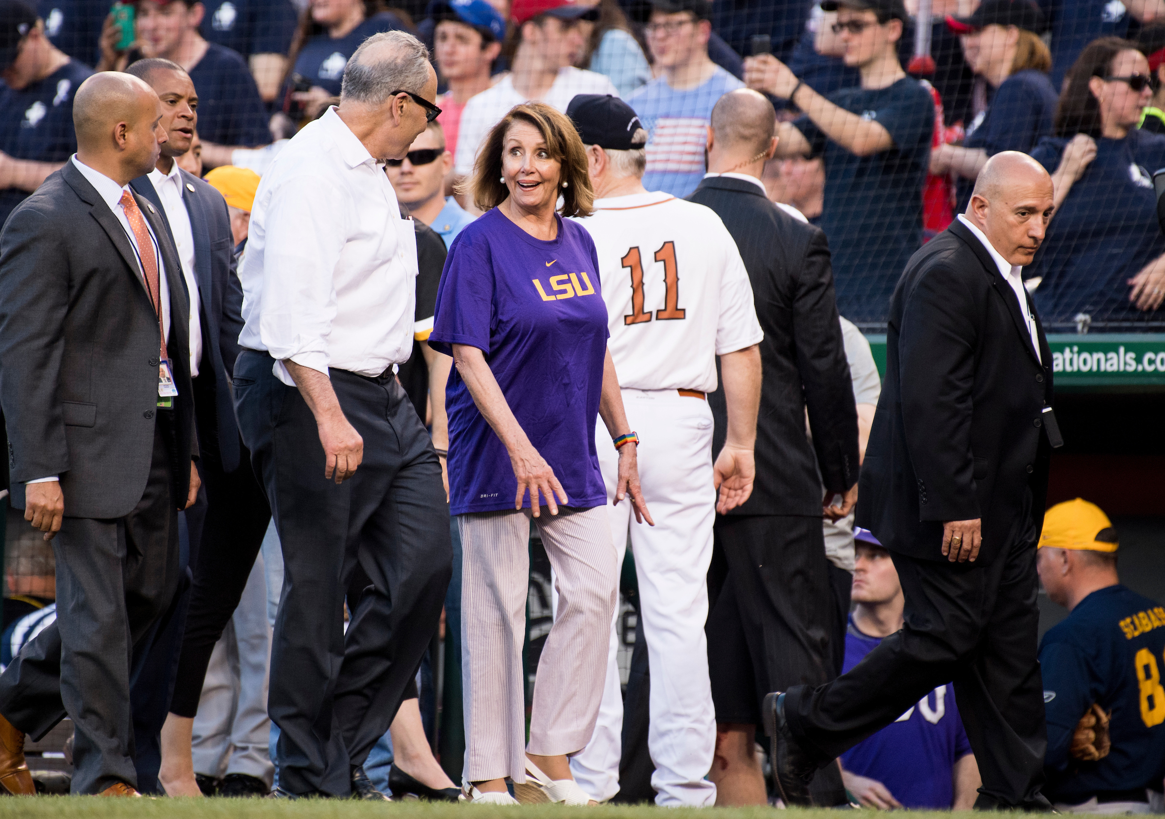 Senate Minority Leader Chuck Schumer, D-N.Y., and House Minority Leader Nancy Pelosi, D-Calif., walk with their Capitol Police security detail on the field before the start of the game. (Bill Clark/CQ Roll Call)