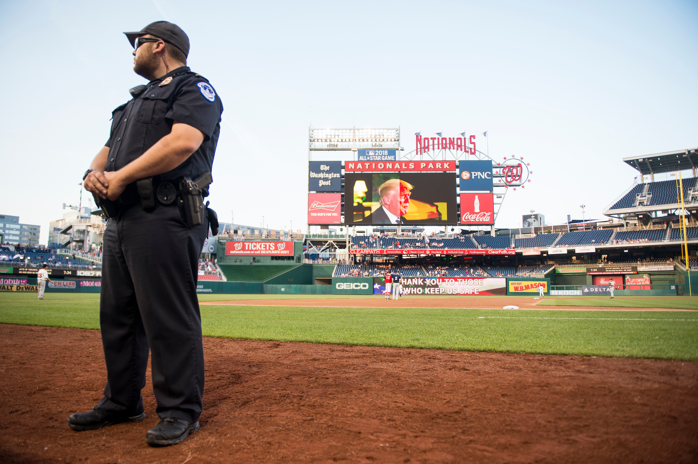 UNITED STATES - JUNE 15: A Capitol Police officer guards the field as President Donald Trump's video message to the crowd plays on the scoreboard during the annual Congressional Baseball Game at Nationals Park in Washington on Thursday, June 15, 2017. (Photo By Bill Clark/CQ Roll Call)