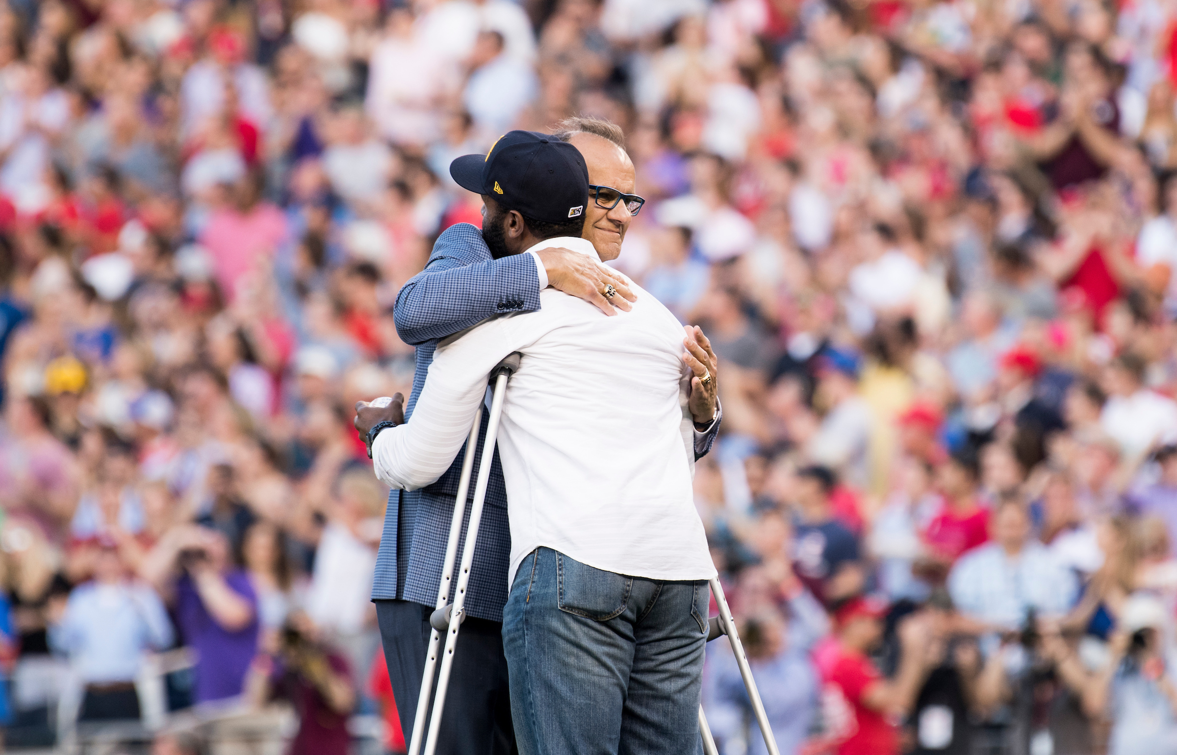 Former New York Yankees manager Joe Torre gives a hug to David Bailey, one of the the injured Capitol Police officers on Rep. Steve Scalise's security detail, before Bailey threw out the first pitch at the annual Congressional Baseball Game. (Bill Clark/CQ Roll Call)