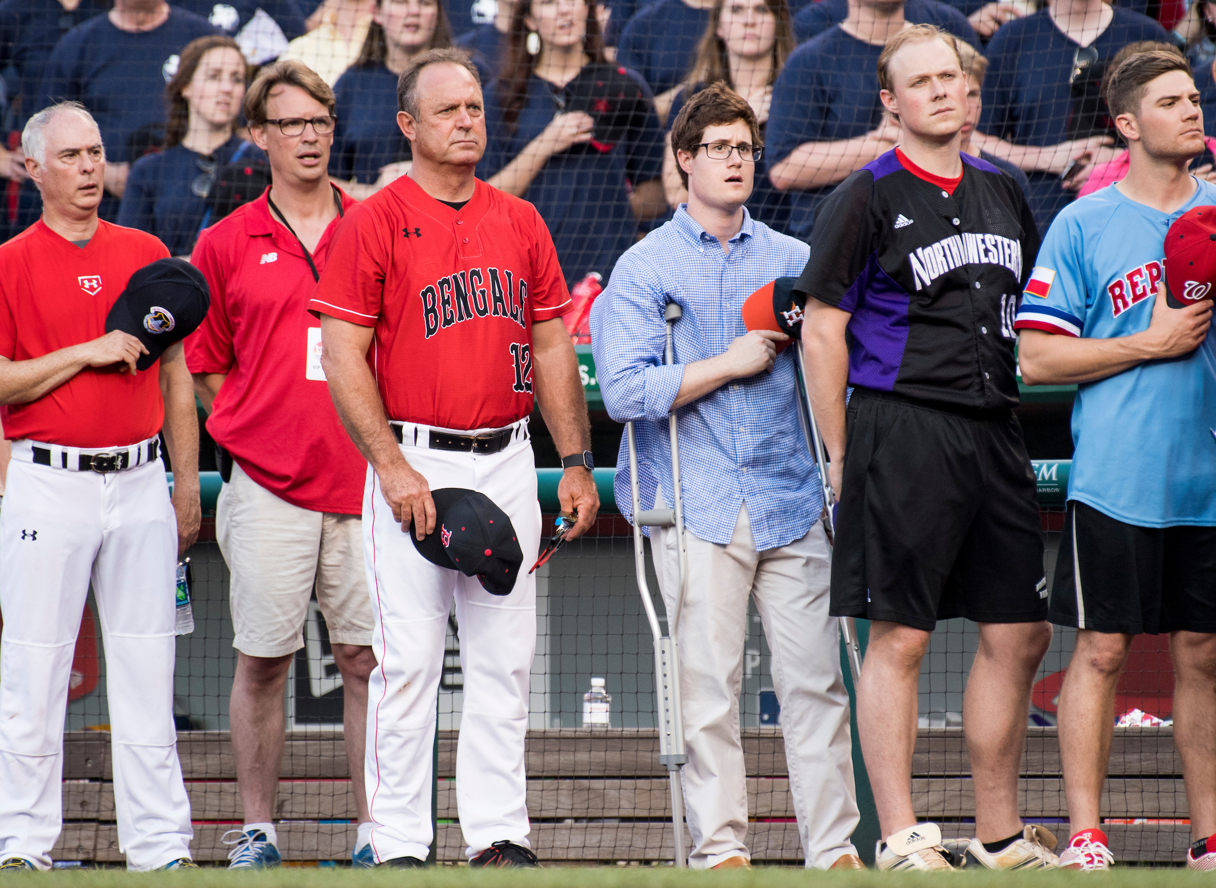 Congressional staffer Zach Barth, center, injured at the baseball practice shooting the day before, stands at the beginning of the game in Washington on Thursday. (Bill Clark/CQ Roll Call)