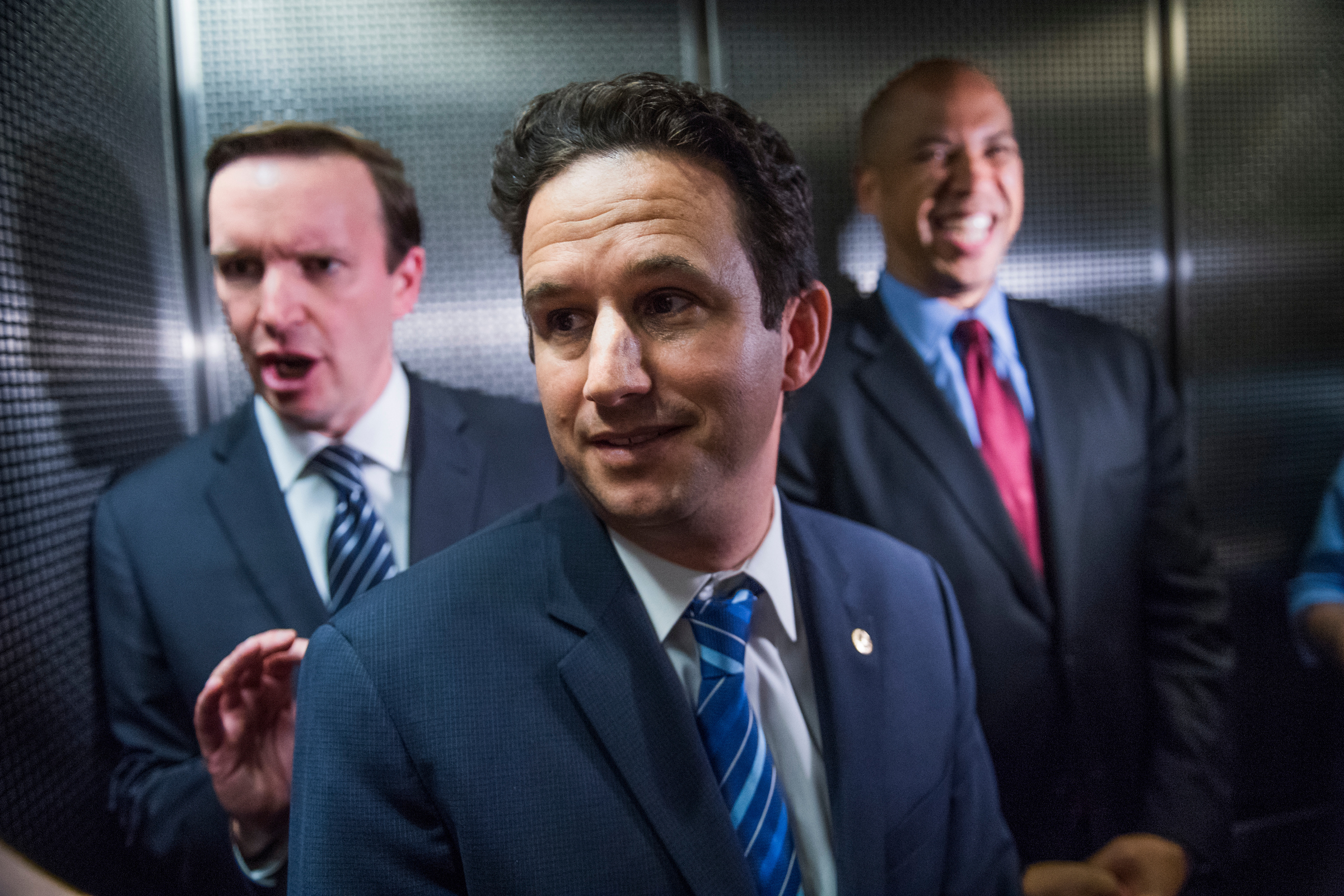 UNITED STATES - JUNE 20: From left, Sens. Chris Murphy, D-Conn., Brian Schatz, D-Hawaii, and Cory Booker, D-N.J., ride an elevator in Ford Building before a meeting with Congressional Budget Office Director Keith Hall where they asked for a copy of the Republicans' health care bill on June 20, 2017. (Photo By Tom Williams/CQ Roll Call)