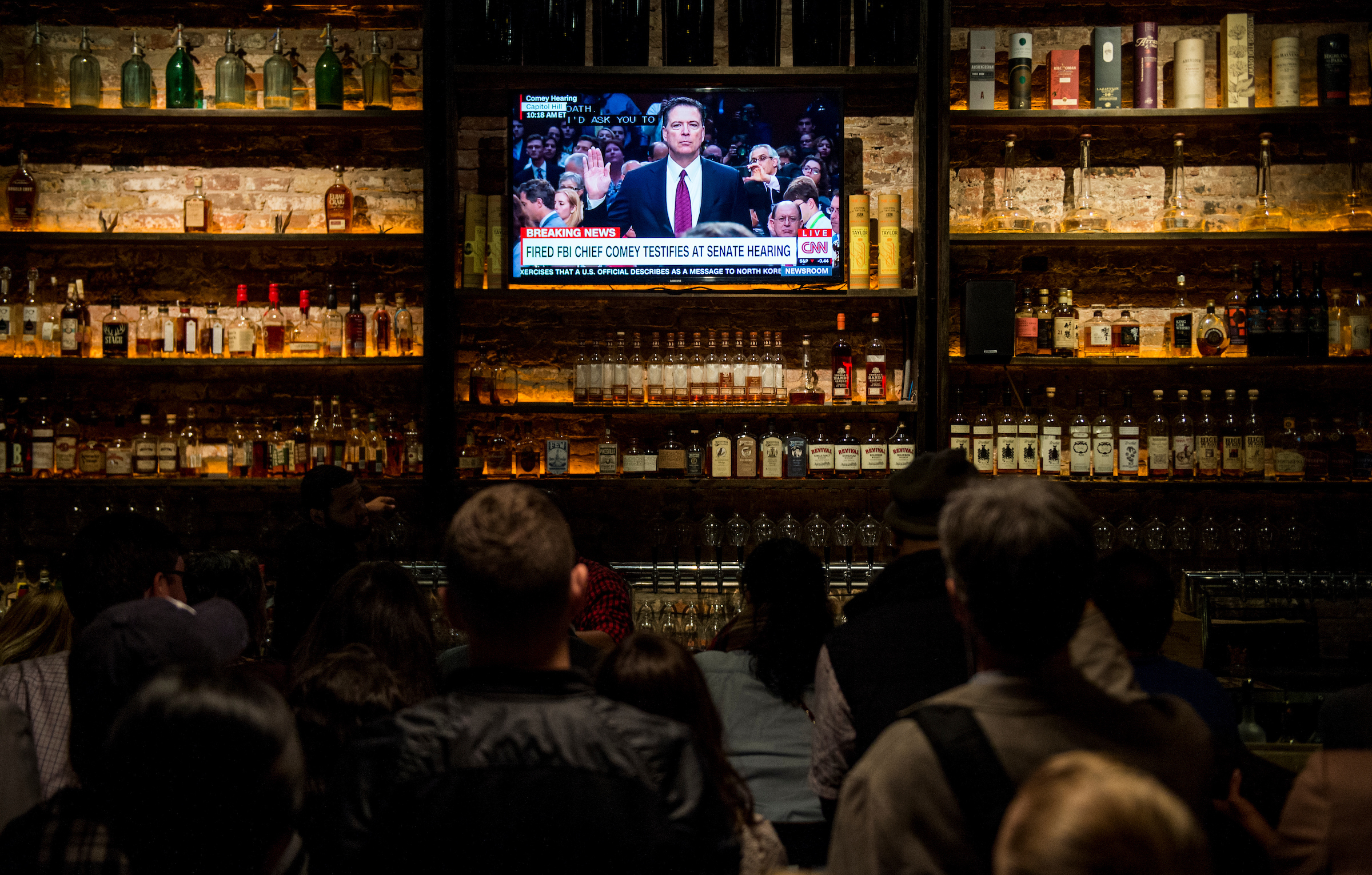 The crowd gathered at The Partisan bar watch as former FBI Director James B. Comey arrives to testify during the Senate Select Intelligence Committee hearing on Thursday. (Bill Clark/CQ Roll Call)