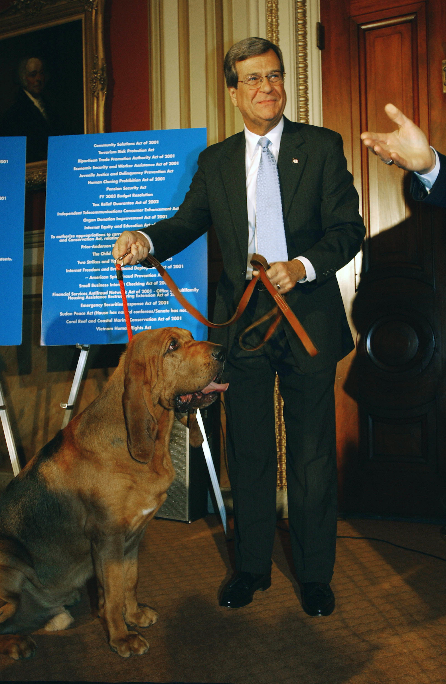 "Senate Majority Leader Trent Lott, R-Miss., with bloodhounds at a news conference of GOP Senate leadership criticizing the Democratic leadership on its handling of the Senate agenda. As Lott and others entered the room with the dogs, they coaxed the dogs to ""find"" legislation that has not yet come to the Senate floor..CONGRESSIONAL QUARTERLY PHOTO BY SCOTT J. FERRELL"