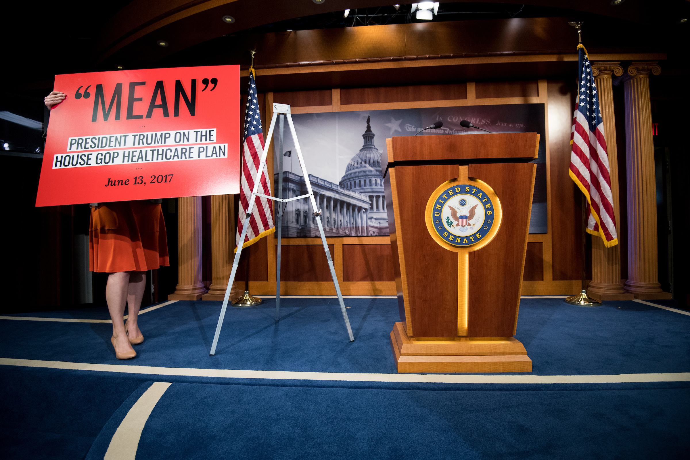 A staffer places a poster on an easel in preparation for the press conference with Senate Minority Leader Chuck Schumer, D-N.Y., Sen. Patty Murray, D-Wash., and Sen. Ron Wyden, D-Ore., on the Senate Republicans' health care bill in the Capitol on Thursday. (Bill Clark/CQ Roll Call)