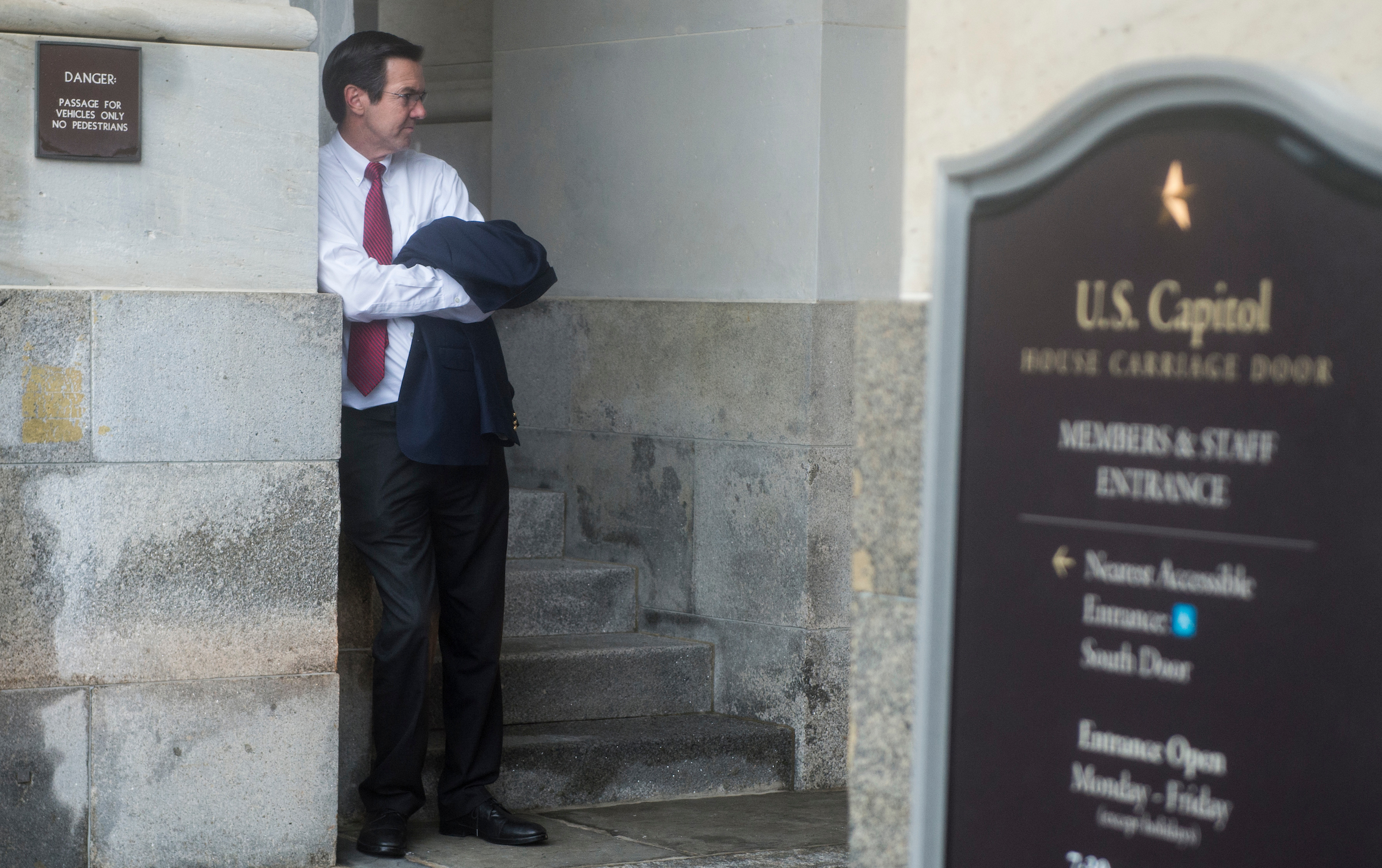 UNITED STATES - JULY 28: Rep. Evan Jenkins, R-W.Va., takes shelter from the rain under the carriage entrance as he waits for his ride following the final votes as Congress leaves town for their summer recess on Friday, July 28, 2017. (Photo By Bill Clark/CQ Roll Call)