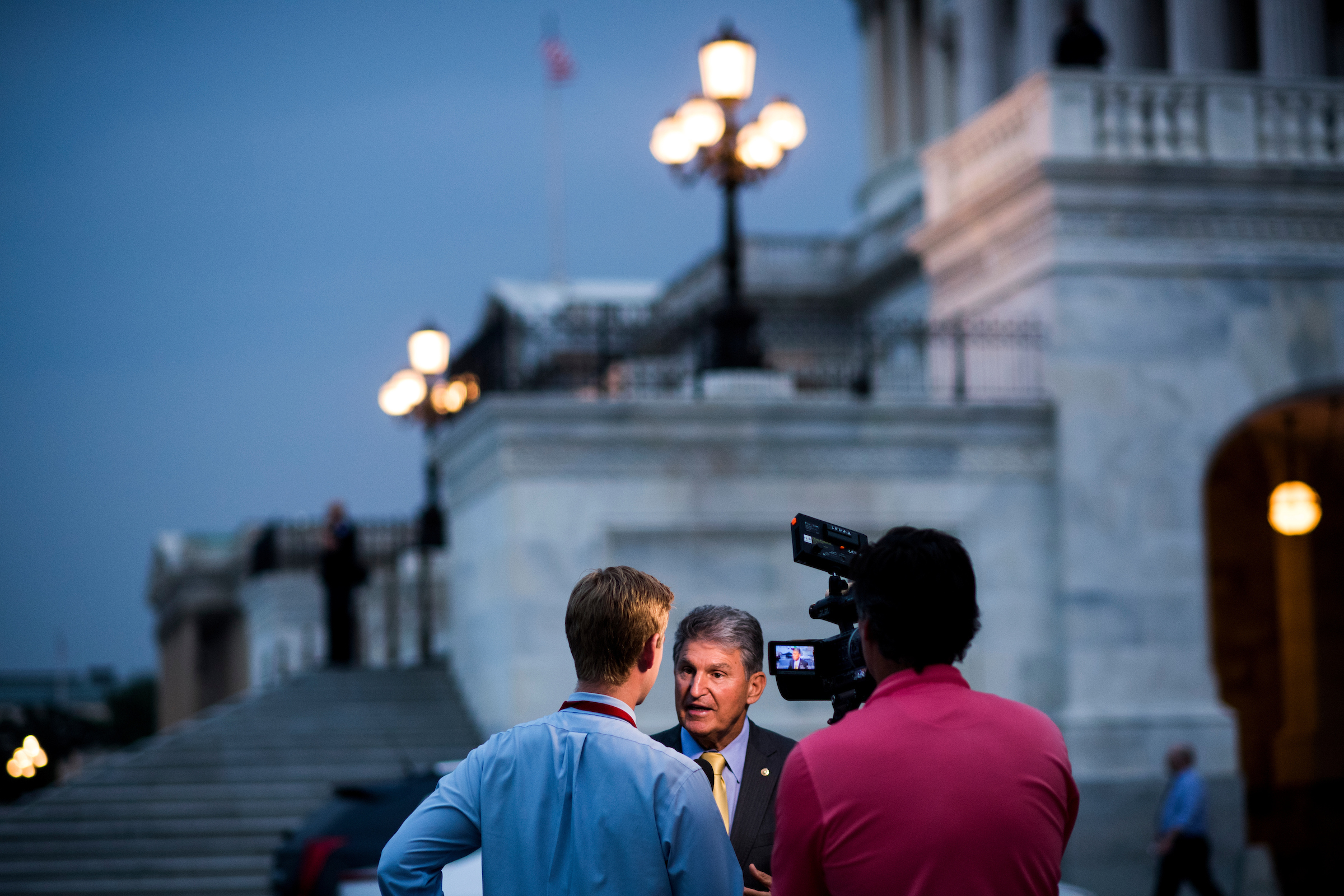 8:17 p.m. | Sen. Joe Manchin III, D-W.Va., talks to a news crew outside of the Capitol before the Senate begins its vote-a-rama night. (Bill Clark/CQ Roll Call)