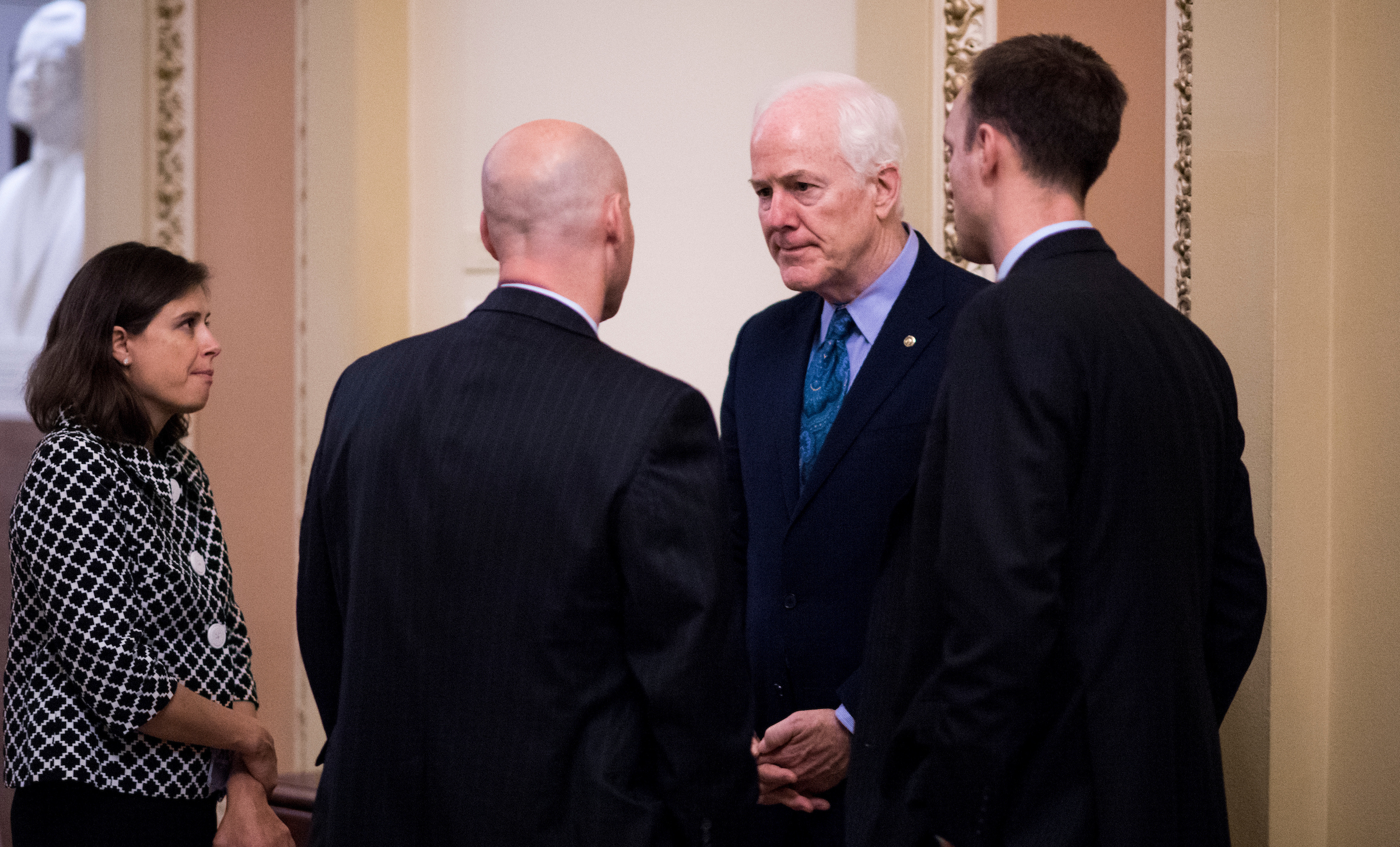 9:24 p.m. | Sen. John Cornyn, R-Texas, center right, speaks with President Trump's director of legislative affairs Mark Short, center left, outside of the Senate floor. (Bill Clark/CQ Roll Call)