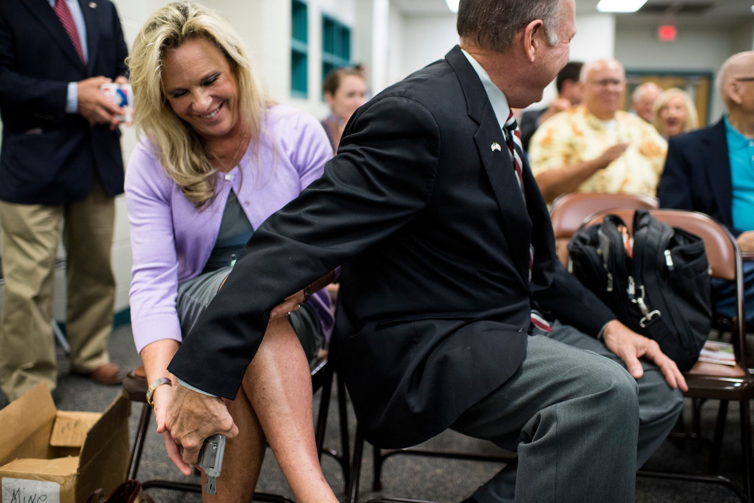 GOP candidate for U.S. Senate Roy Moore returns his wife's hand gun to her after displaying it as a way to show support for the 2nd amendment after candidates were asked about their views on gun rights during a candidates' forum in Valley, Ala., on Thursday, Aug. 3, 2017. The former Chief Justice of the Alabama Supreme Court is running tin the special election to fill the seat vacated by Attorney General Jeff Sessions. (Bill Clark/CQ Roll Call)
