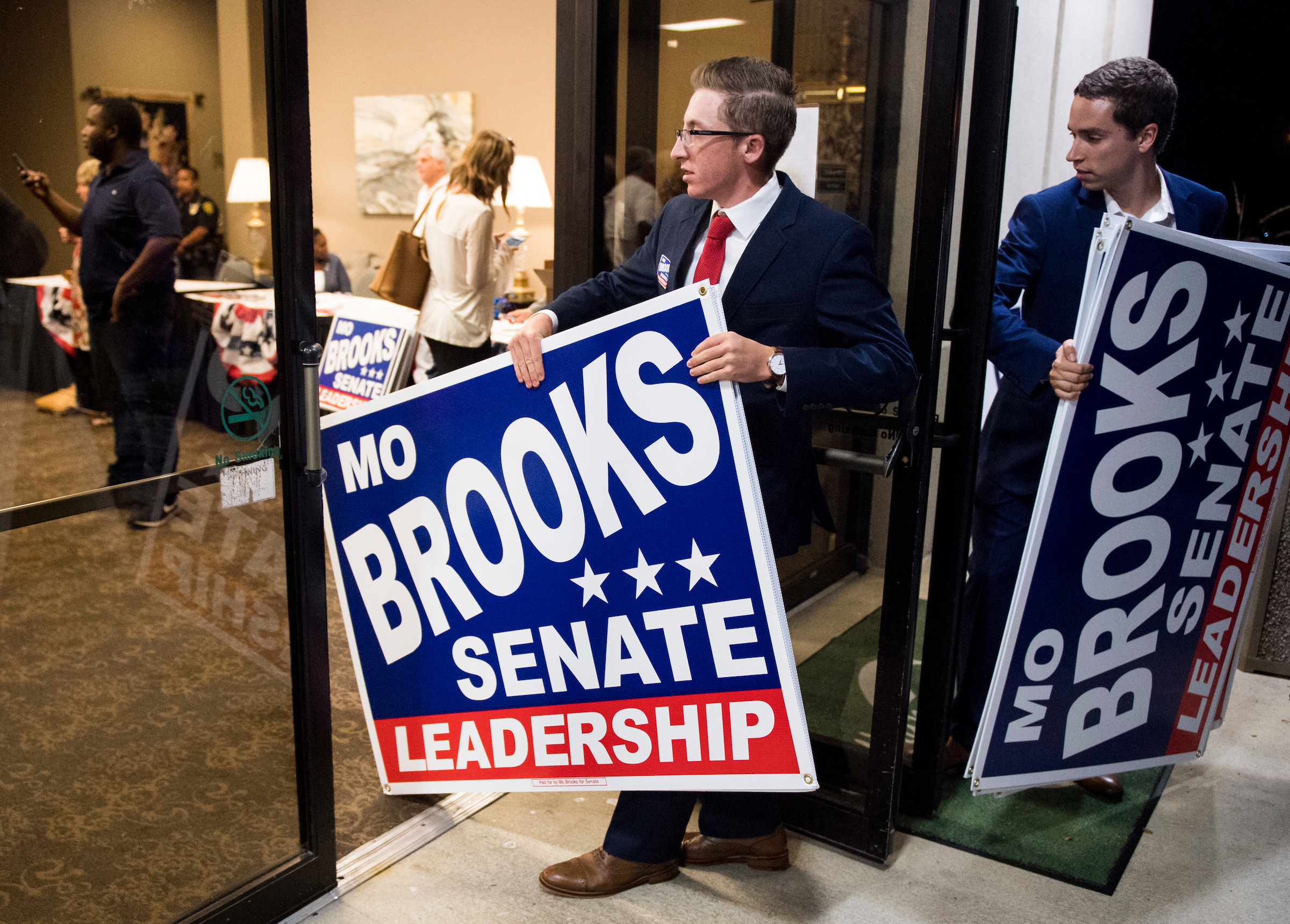 Campaign workers for Rep. Mo Brooks, R-Ala., carry campaign signs out of the building after the U.S. Senate candidate forum held by the Shelby County Republican Party in Pelham, Ala., on Friday. (Bill Clark/CQ Roll Call)