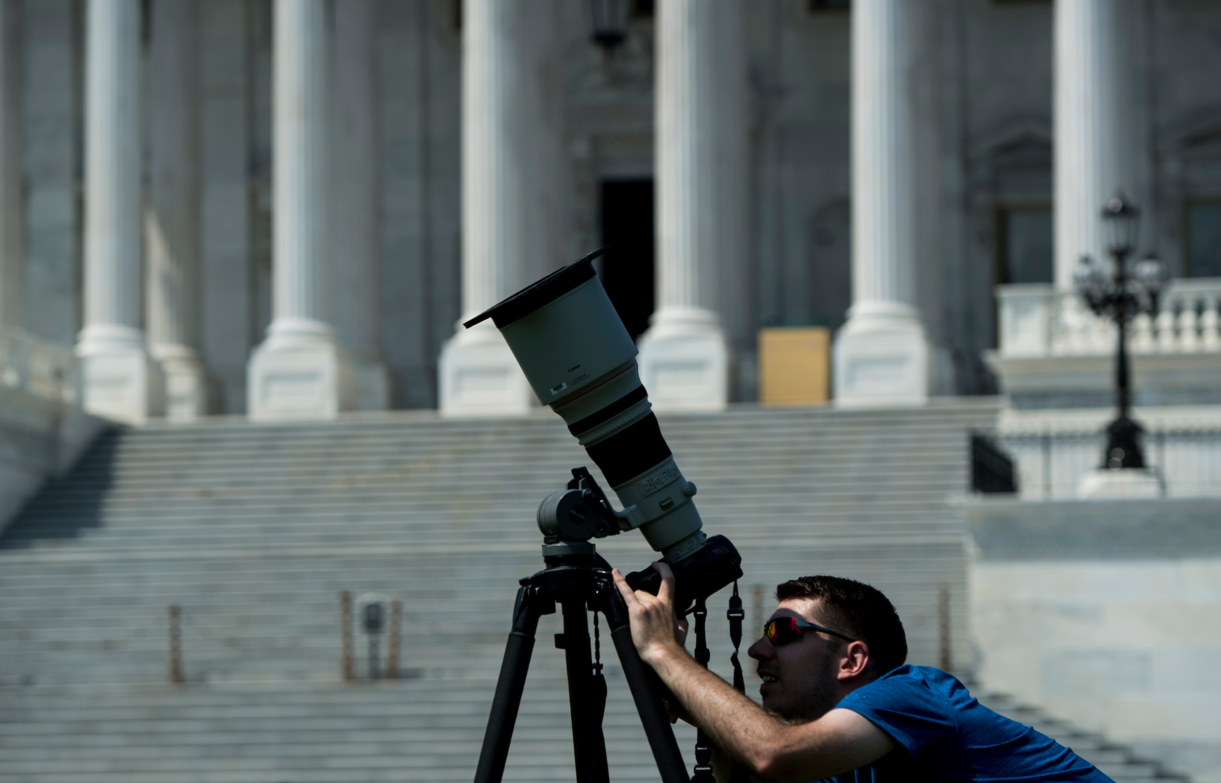 UNITED STATES - AUGUST 21: A news photographer adjusts his telephoto lens equipped with a filter in front of the U.S. Capitol on Monday, Aug. 21, 2017, in preparation for today's solar eclipse. (Photo By Bill Clark/CQ Roll Call)