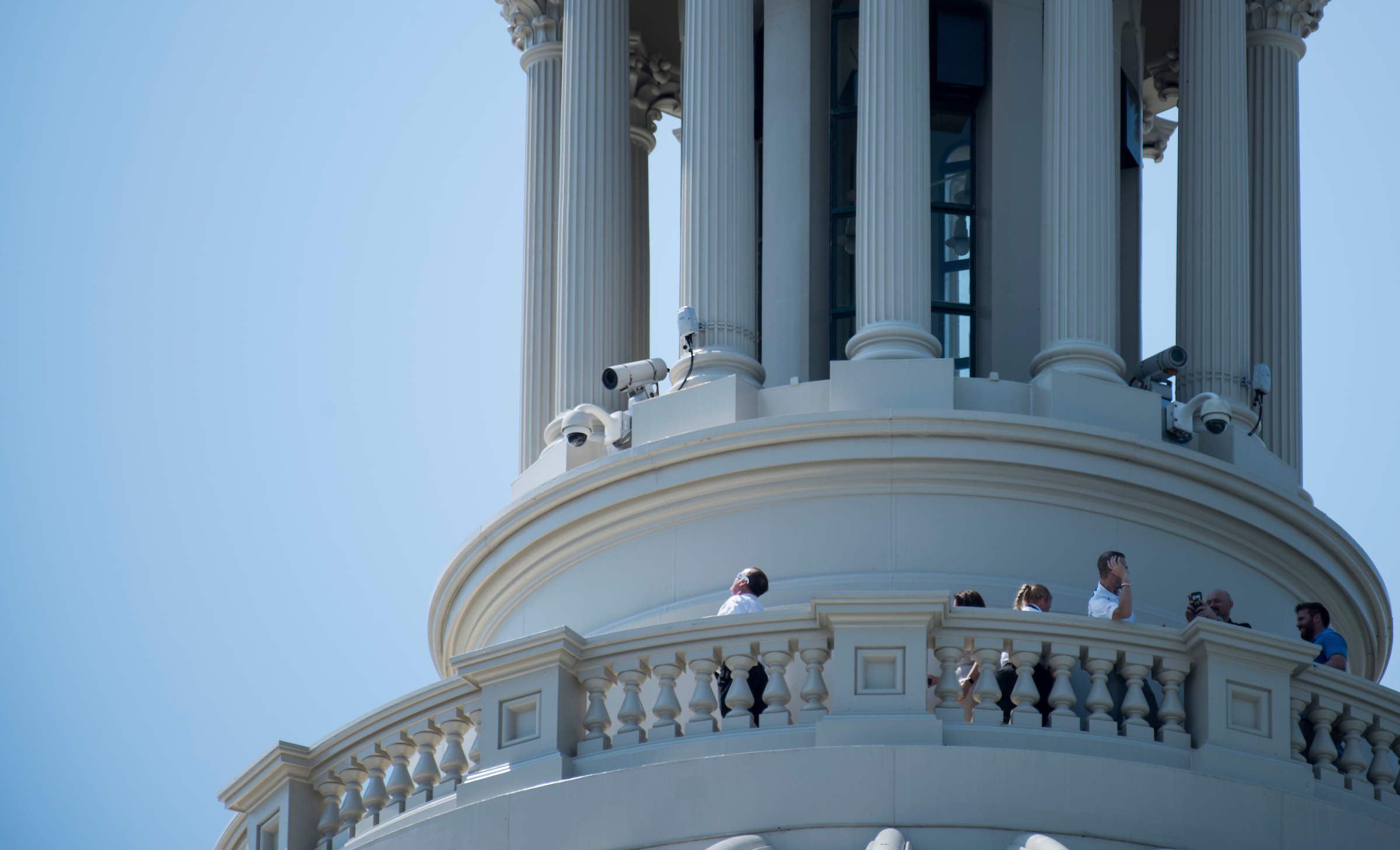 UNITED STATES - AUGUST 21: A man on a dome tour of the U.S. Capitol uses his eclipse sun glasses to look at the sun from the top of the Capitol building on Monday, Aug. 21, 2017, just before the start of today's solar eclipse. (Photo By Bill Clark/CQ Roll Call)