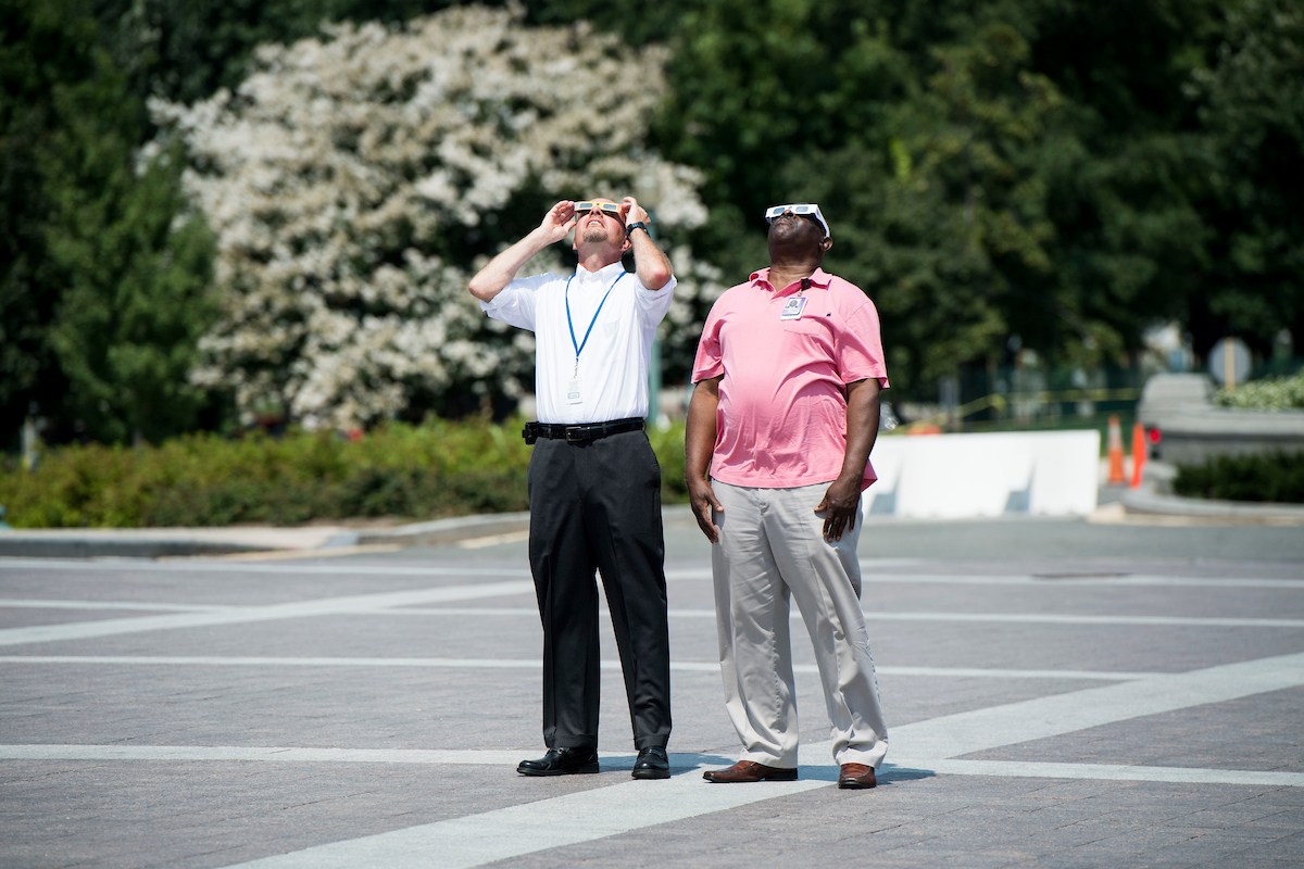 Two Capitol staffers stand on the East Plaza of the U.S. Capitol testing their solar eclipse glasses on Monday, Aug. 21, 2017, minutes before the start of today's solar eclipse. (Bill Clark/CQ Roll Call)