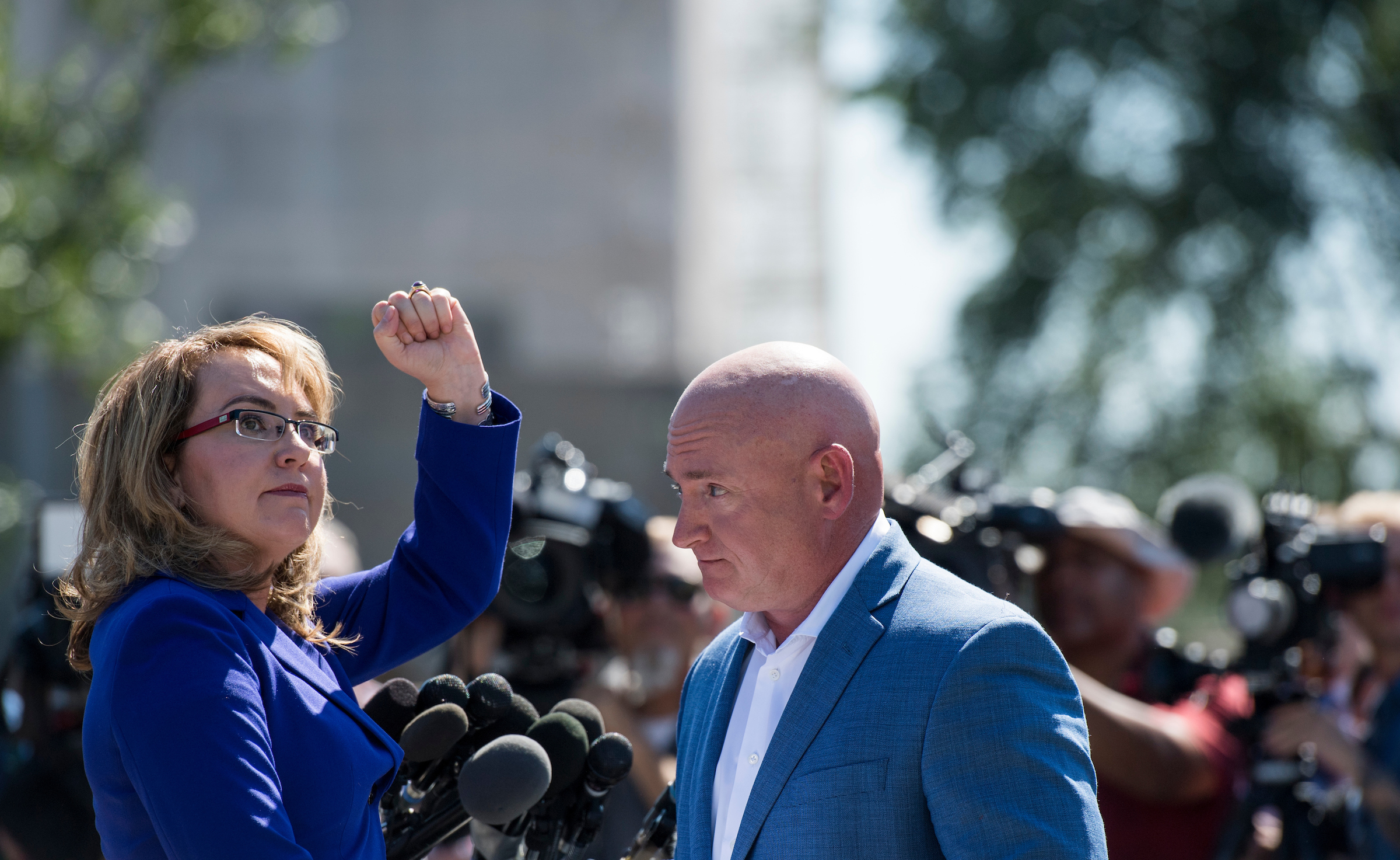 UNITED STATES - OCTOBER 2: Former Congresswoman Gabrielle Giffords, D-Ariz., turns to shake her fist at the Capitol as her husband retired NASA astronaut Captain Mark Kelly looks on during their news conference at the U.S. Capitol on Monday, Oct. 2, 2017, to respond to last night's tragic mass shooting in Las Vegas, NV. They are the Co-Founders of Americans for Responsible Solutions. (Photo By Bill Clark/CQ Roll Call)