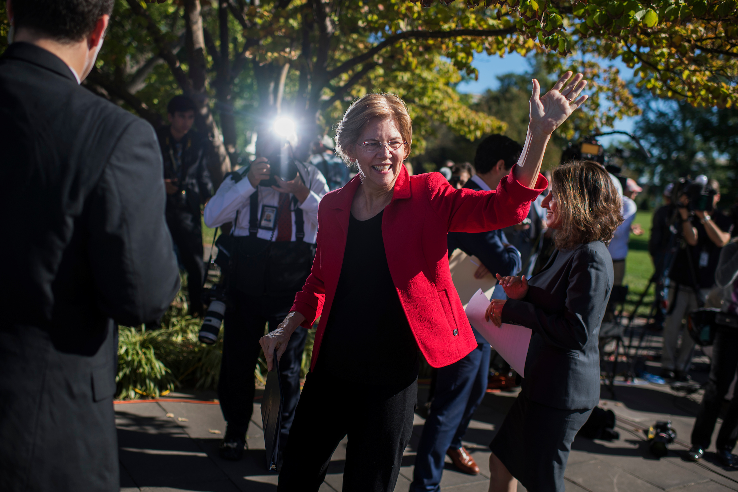 UNITED STATES - OCTOBER 18: Sen. Elizabeth Warren, D-Mass., waves to tourists after a news conference on the east lawn of the Capitol on a CAP Action report saying that wealthy Americans, such as President Trump and his cabinet, would benefit from the GOP tax and budget proposals at the expense of the middle class on October 18, 2017. (Photo By Tom Williams/CQ Roll Call)