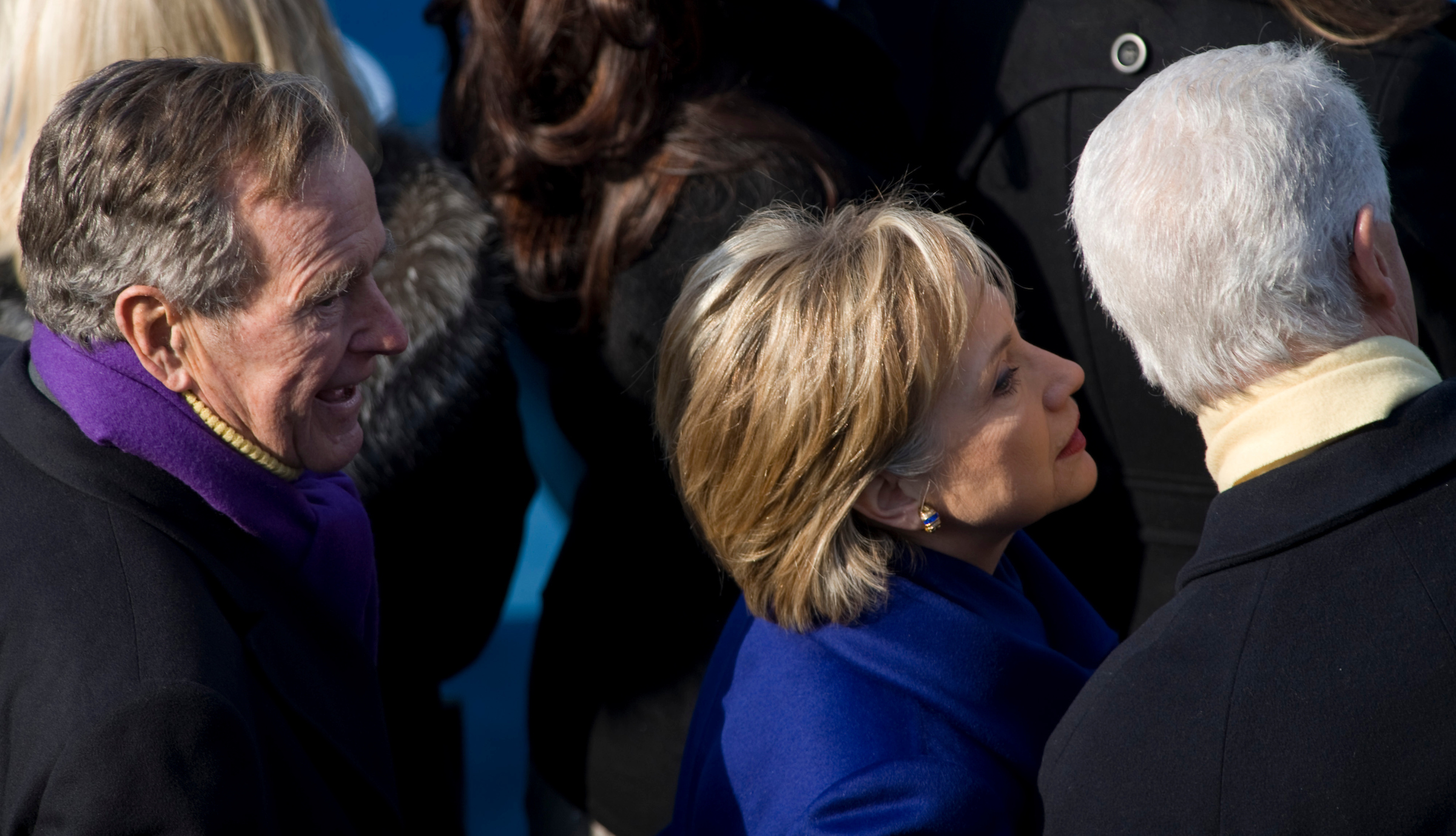 Former President George Bush watches and Hillary Clinton whispers in Former President Bill Clinton's ear during the Inauguration Ceremony for President Barack Obama on the West Front of the U.S. Capitol on Tuesday, Jan. 20, 2009. (CQ Roll Call Archive Photo)