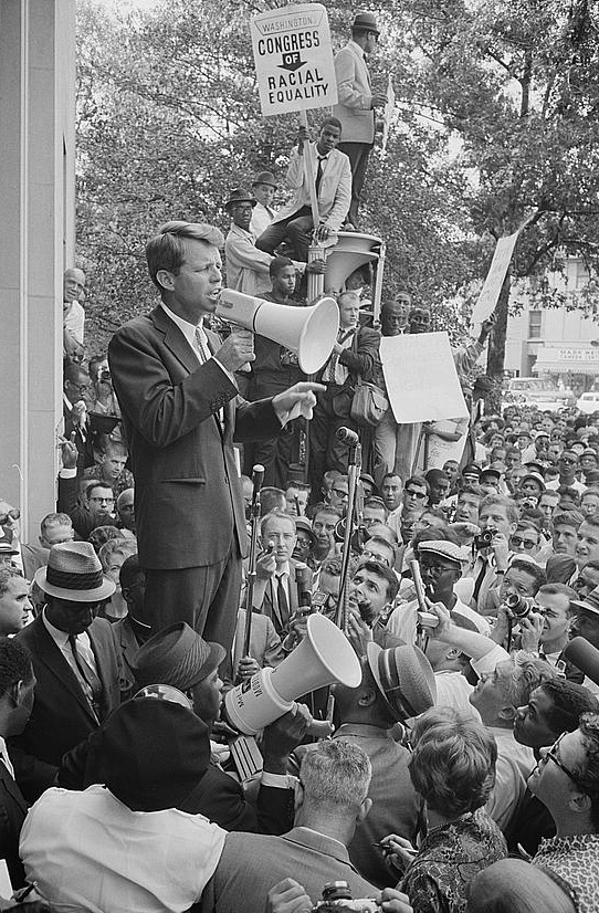Photograph showing Attorney General Robert F. Kennedy speaking to a crowd of African Americans and whites through a megaphone outside the Justice Department; sign for Congress of Racial Equality is prominently displayed.