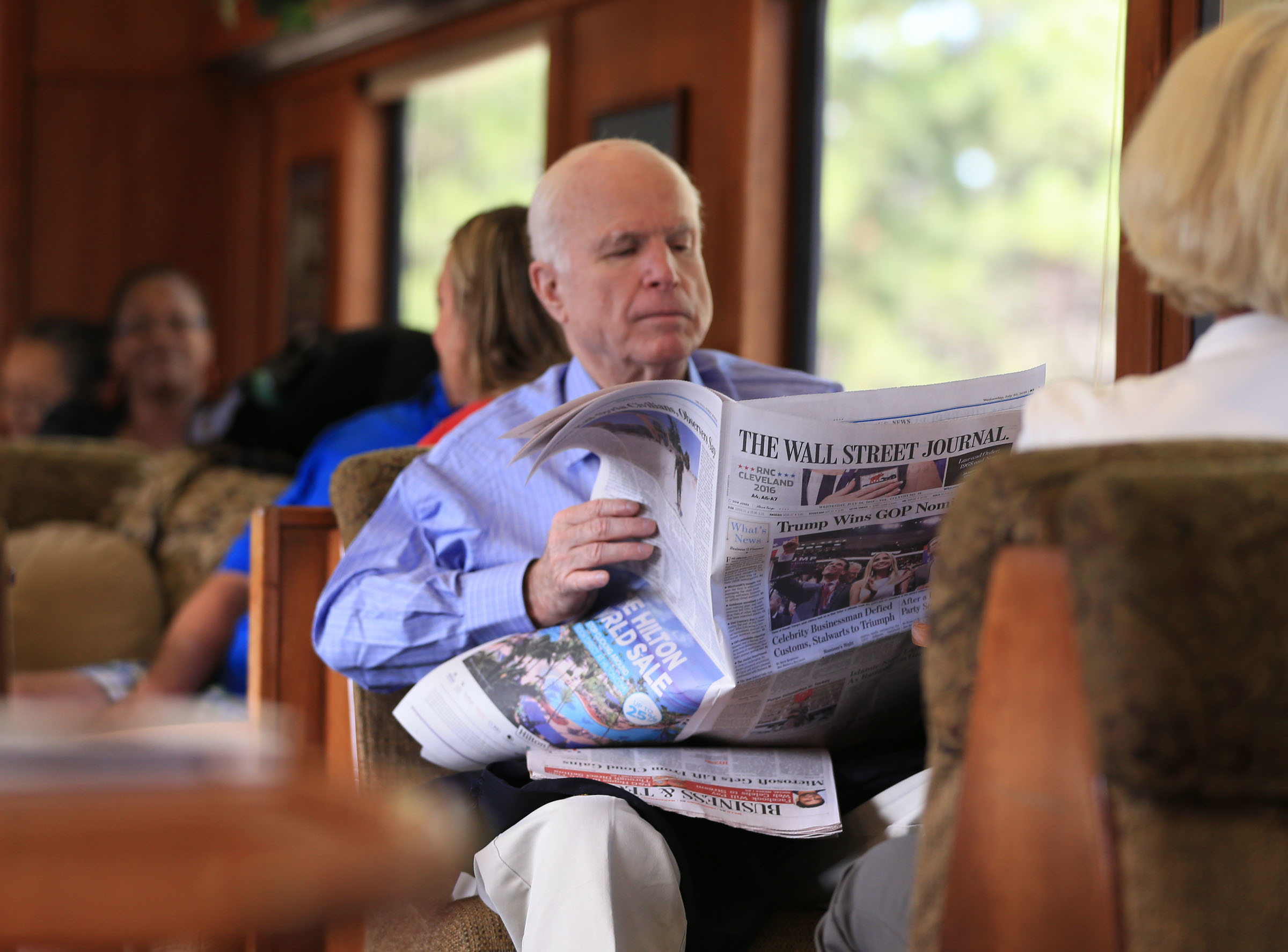 United States Senator John McCain reads the headlines announcing Trump's Republican National Convention victory as the party's nominee as he rides the train to the Grand Canyon out of Williams, Arizona Wednesday morning. (Photograph by Daniel A. Anderson)