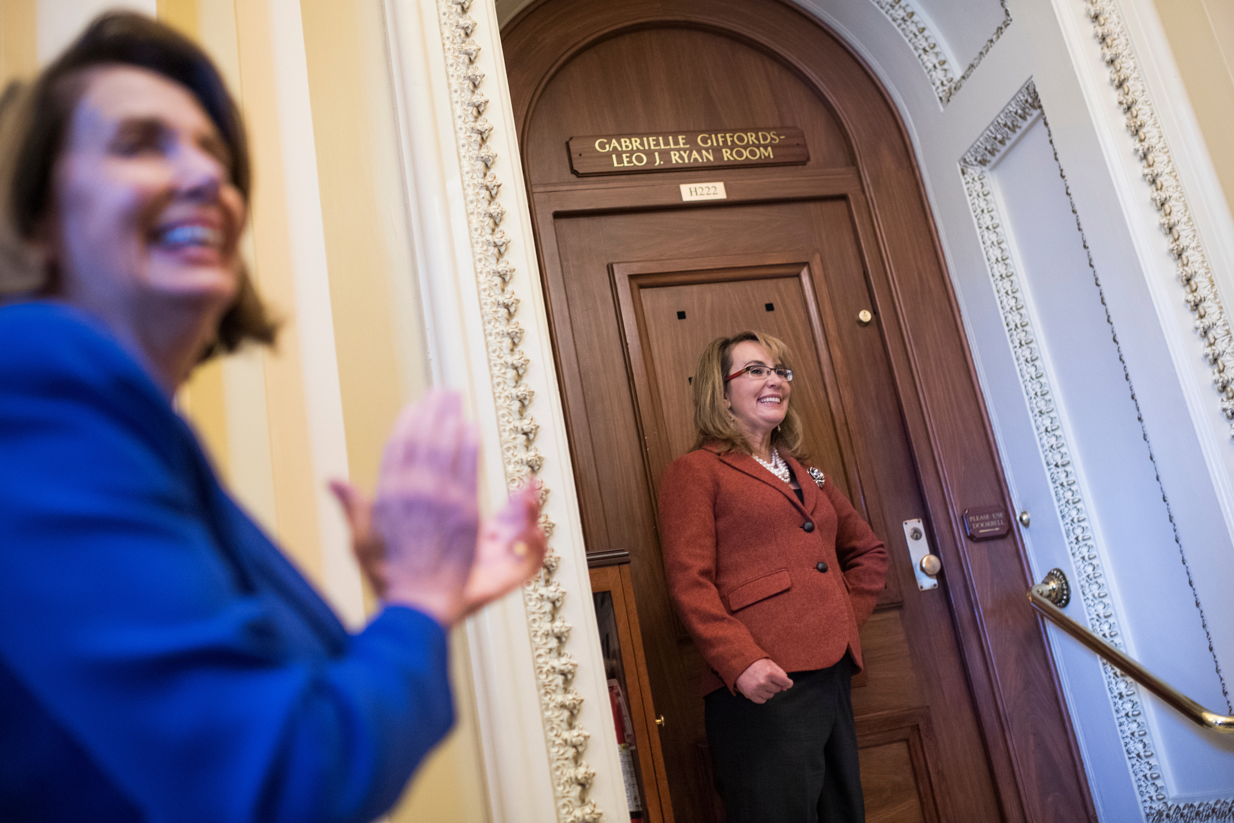 : Former Rep. Gabrielle Giffords, D-Ariz., poses outside the House Democratic Cloakroom in the Capitol as House Minority Leader Nancy Pelosi, D-Calif., looks on, on November 15, 2017, which was named in honor of Giffords and the late Rep. Leo Ryan, D-Calif., who were victims of gun violence. Ryan was killed in the 1978 Jonestown massacre and his aide, Rep. Jackie Speier, D-Calif., was wounded, and Giffords was wounded in the 2011 Tucson shooting. (Photo By Tom Williams/CQ Roll Call)