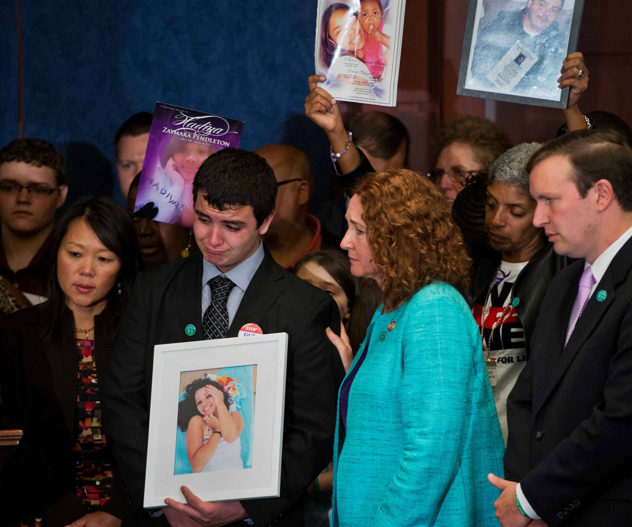 UNITED STATES - SEPTEMBER 18: Rep. Elizabeth Esty, D-Conn., comforts Carlos Soto, whose sister Victoria was a teacher killed in the Sandy Hook Elementary shooting, during an event in the Capitol Visitor Center to call on Congress to act on gun control legislation. Sen. Chris Murphy, D-Conn., appears at right. (Photo By Tom Williams/CQ Roll Call)