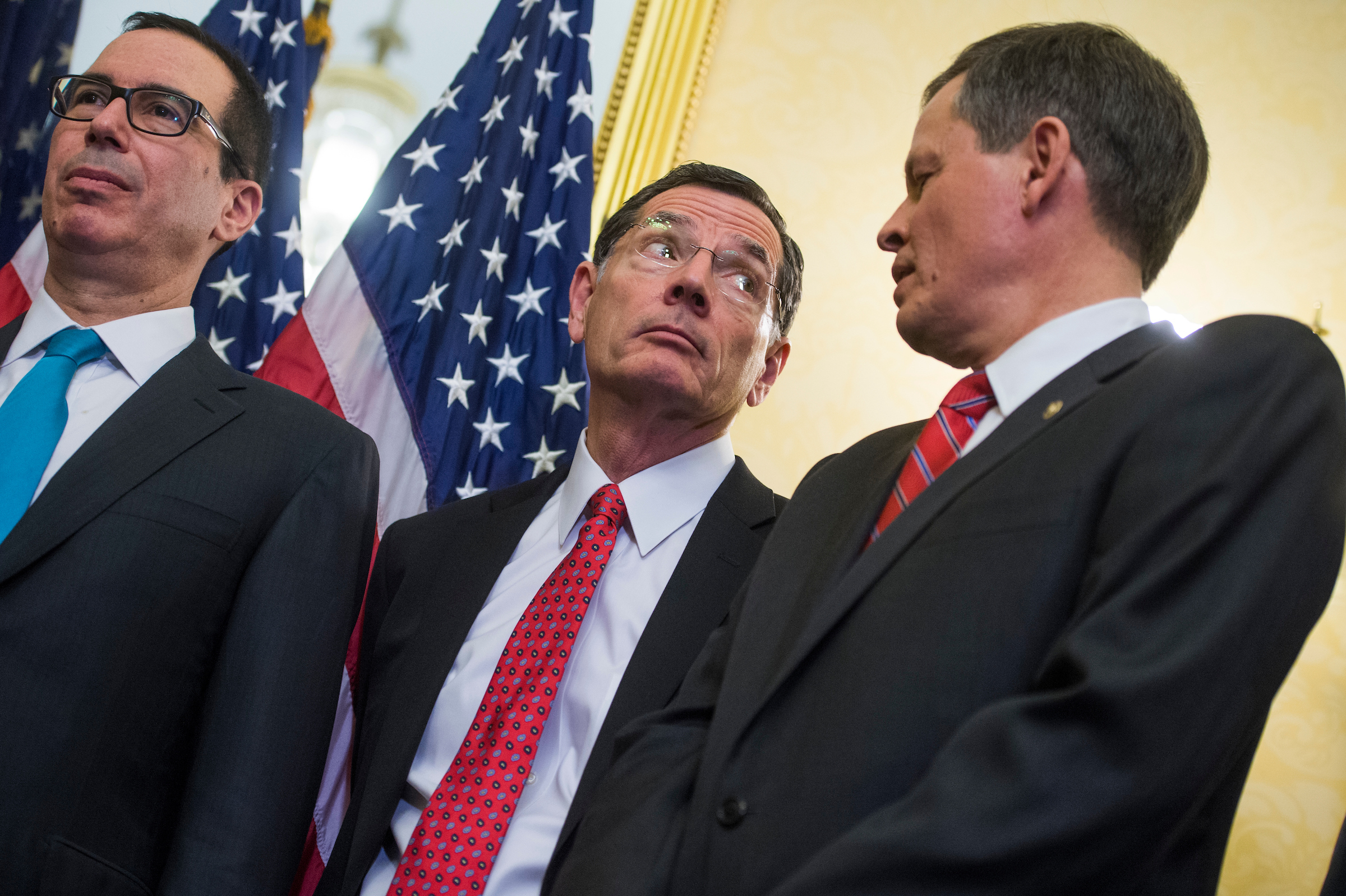 UNITED STATES - NOVEMBER 07: From left, Treasury Secretary Steven Mnuchin, Sens. John Barrasso, R-Wyo., and Steve Daines, R-Mont., attend a news conference in the Capitol where GOP senators said families and small businesses would benefit from tax reform on November 7, 2017. Administration officials and tax experts also voiced support for reform. (Photo By Tom Williams/CQ Roll Call)