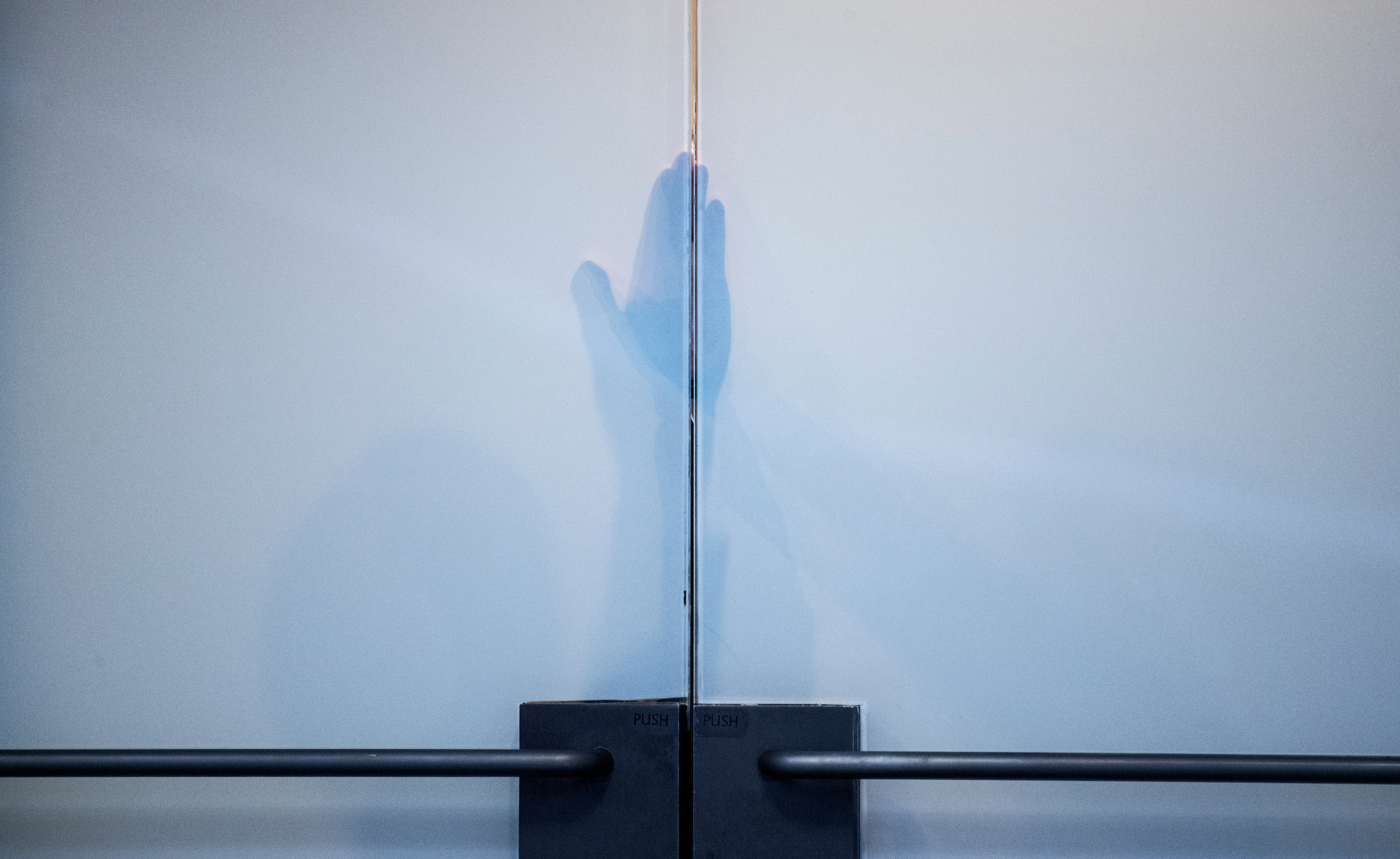 """UNITED STATES - MAY 11: An aide prepares to open the door to a meeting between Deputy Attorney General Rod Rosenstein, Chairman Richard Burr, R-N.C., Ranking Member Mark Warner, D-Va., after a Senate (Select) Intelligence Committee hearing in Hart Building titled """"World Wide Threats"""" on May 11, 2017. (Photo By Tom Williams/CQ Roll Call)"""