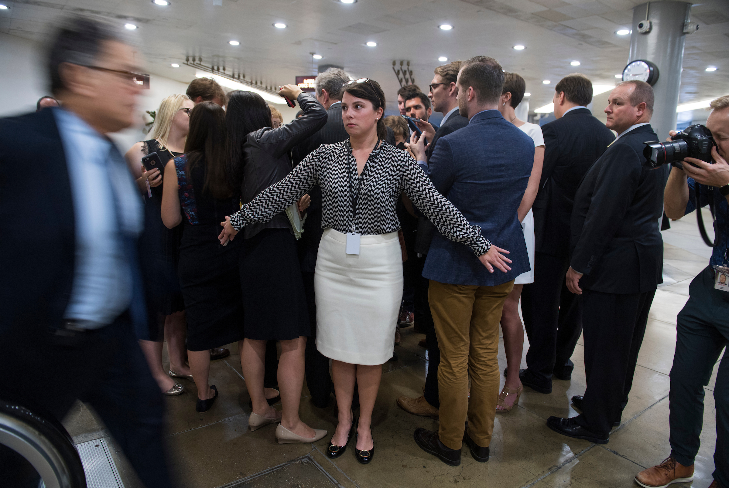 UNITED STATES - OCTOBER 24: Samantha Yeider of the Senate Press Gallery, keeps a path clear for Sen. Al Franken, D-Minn., in the basement of the Capitol on October 24, 2017. (Photo By Tom Williams/CQ Roll Call)