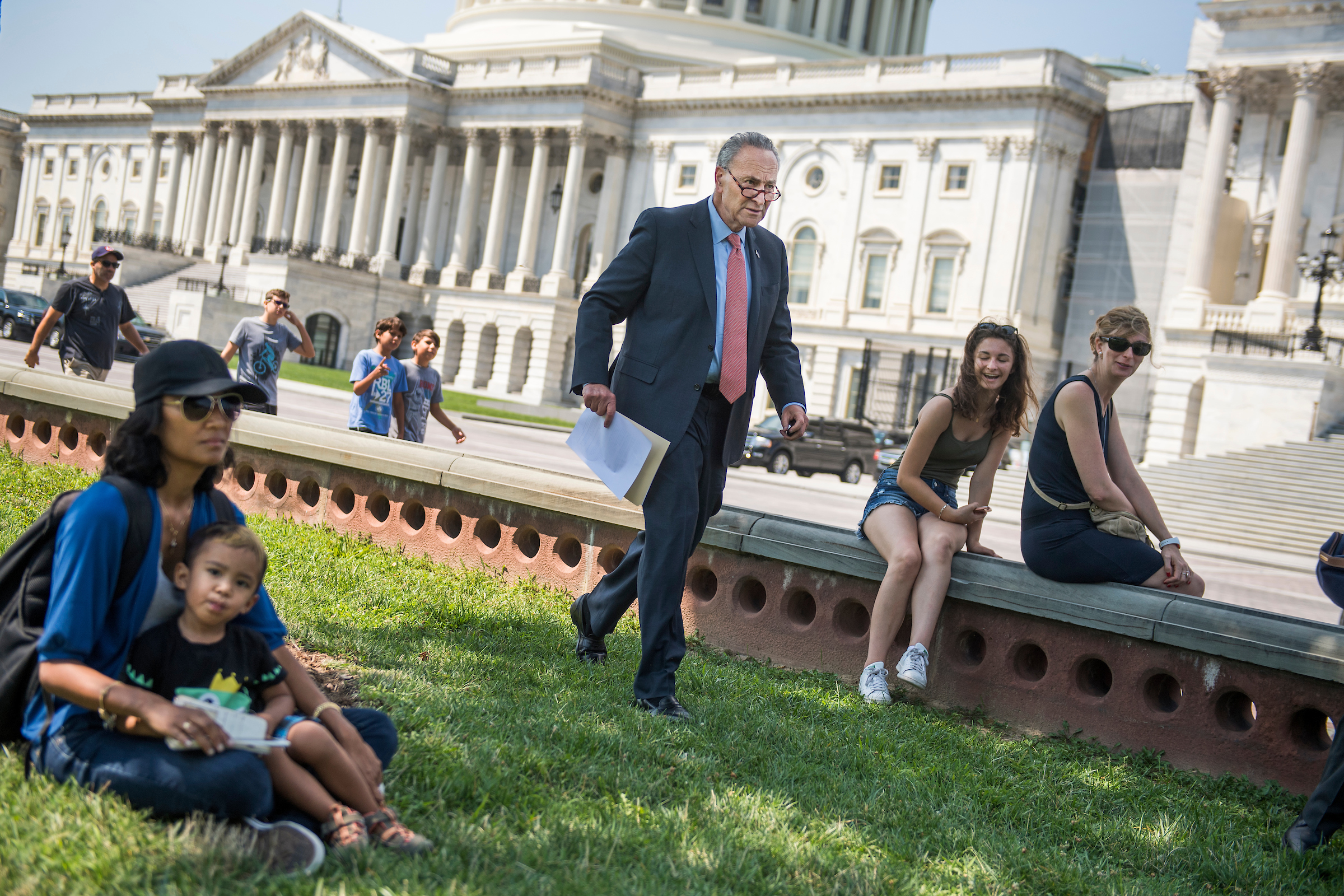 "UNITED STATES - AUGUST 02: Senate Minority Leader Charles Schumer, D-N.Y., returns after a phone call to a news conference on the east lawn of the Capitol to unveil a new economic agenda titled ""A Better Deal on Trade and Jobs"" on August 2, 2017. (Photo By Tom Williams/CQ Roll Call)"