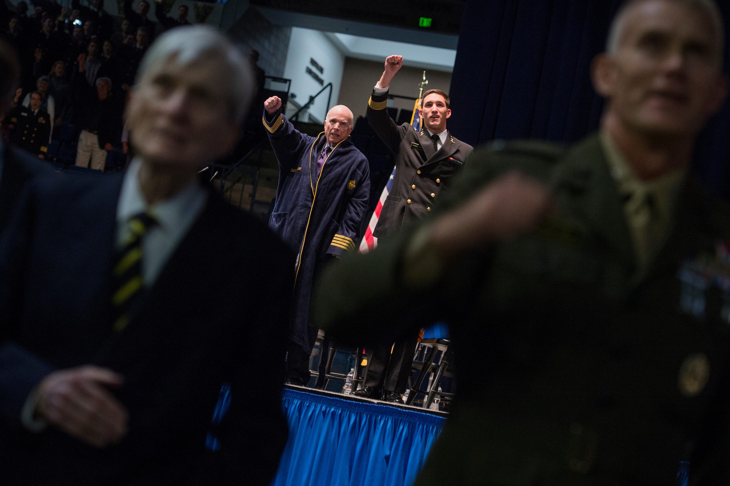October 2017: Sen. John McCain, R-Ariz., and MIDN Brigade Commander Austin Harmel, are seen on stage after McCain and former Sen. John Warner, R-Va., left, who was Secretary of the Navy, addressed the Brigade of Midshipmen at the Naval Academy in Annapolis, Md. McCain's address was almost 50 years to the day that his plane was shot down over Vietnam and he was taken as a prisoner of war. (Photo By Tom Williams/CQ Roll Call)