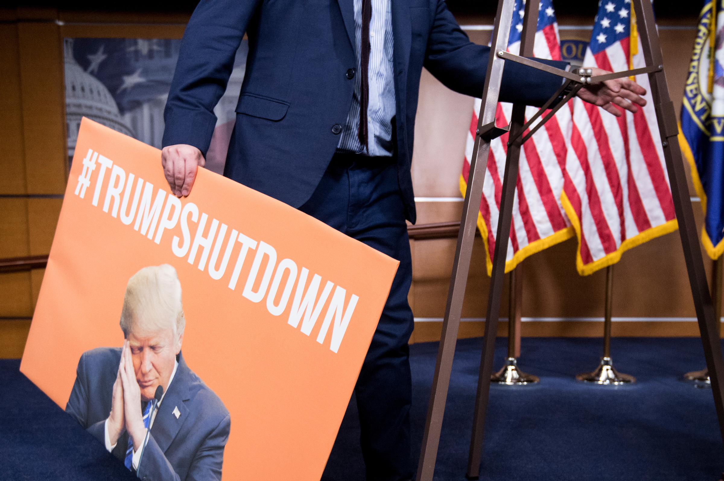 "House Minority Leader Nancy Pelosi's staff sets up a ""#TRUMPSHUTDOWN"" poster before her press conference with women House Democrats in the Capitol as the government shutdown continues on Sunday. The poster was taken down before the press conference started. (Bill Clark/CQ Roll Call)"