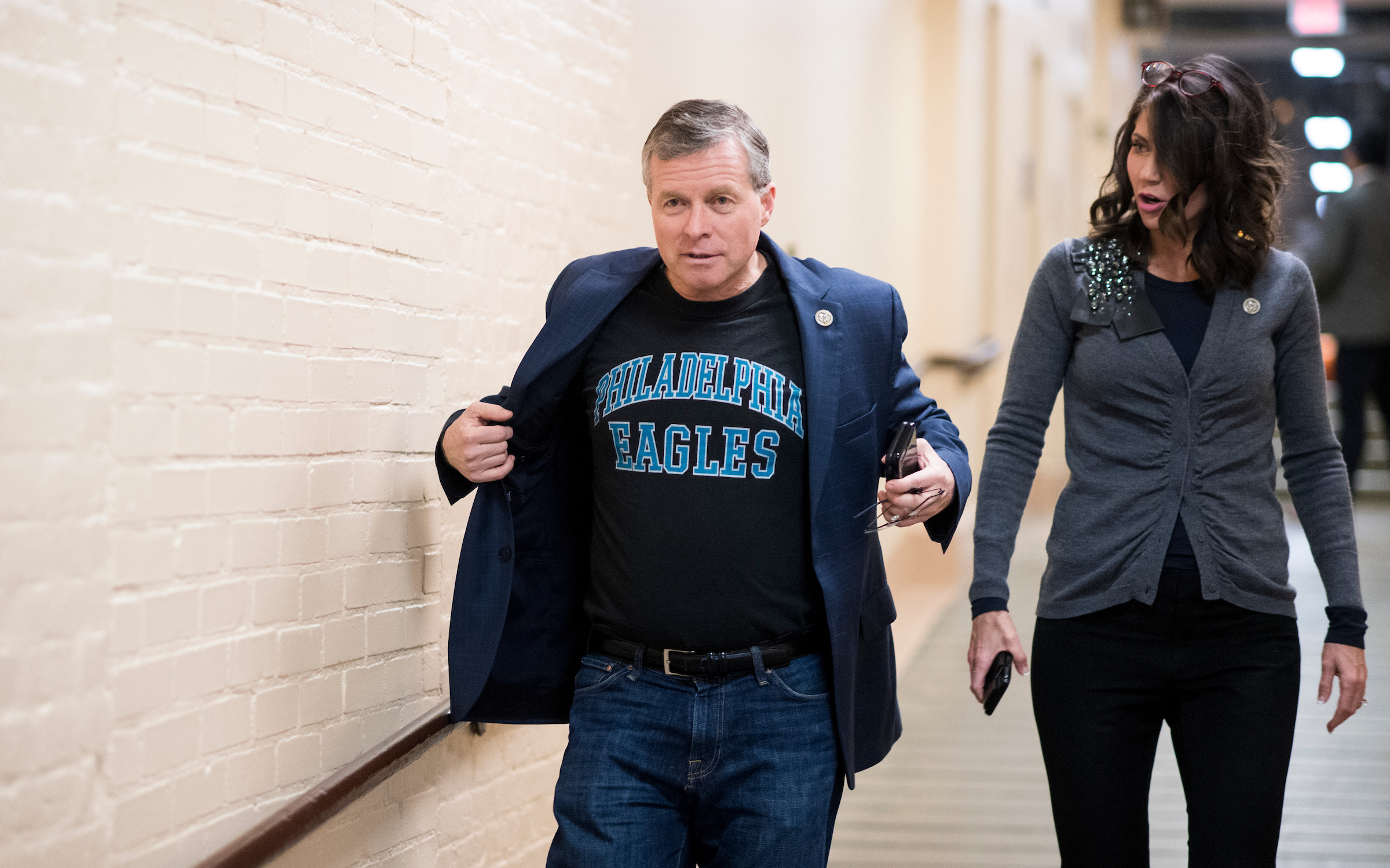 Rep. Charlie Dent, R-Pa., flashes his Philadelphia Eagles shirt as Rep. Kristi Noem, R-S. Dak., looks on as they arrive for the House Republican Conference meeting in the Capitol on Monday. The Philadelphia Eagles will face off against the New England Patriots in the Super Bowl. (Bill Clark/CQ Roll Call)