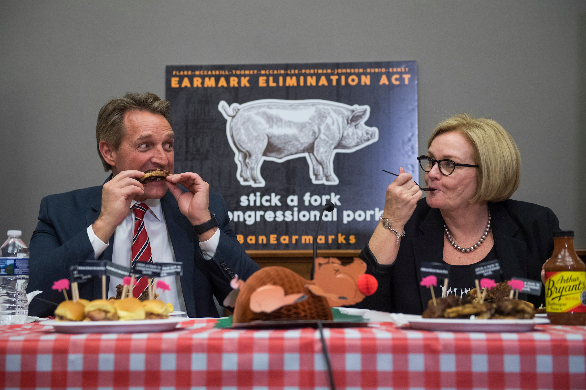 "Sens. Jeff Flake, R-Ariz., and Claire McCaskill, D-Mo., eat barbecue during an event in Russell Building to introduce the Earmark Elimination Act and demonstrate that Congress can ""eat pork without spending it,"" on Wednesday. (Tom Williams/CQ Roll Call)"