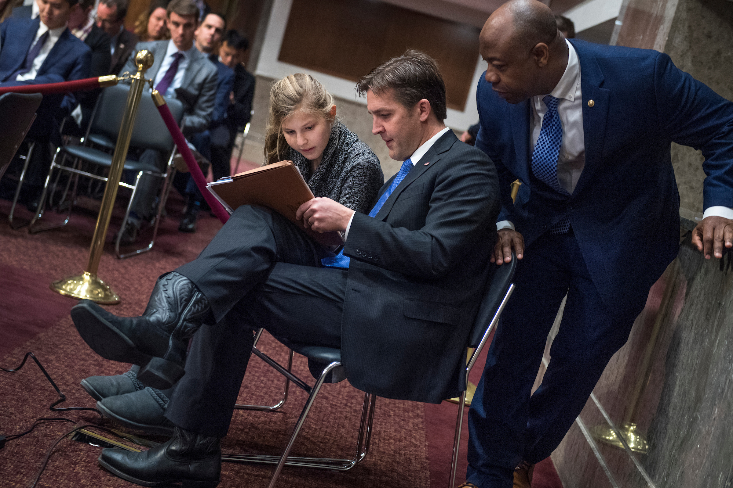 "Sen. Ben Sasse, R-Neb., helps his daughter Alexandra, 14, with algebra homework as Sen. Tim Scott, R-S.C., looks on, during a Senate Armed Services Committee hearing in Dirksen Building titled ""Global Challenges and U.S. National Security Strategy,"" featuring testimony by former Secretary of State Henry Kissinger, former Secretary of State George Shultz, and former Deputy Secretary of State Richard Armitage, on Thursday. (Tom Williams/CQ Roll Call)"