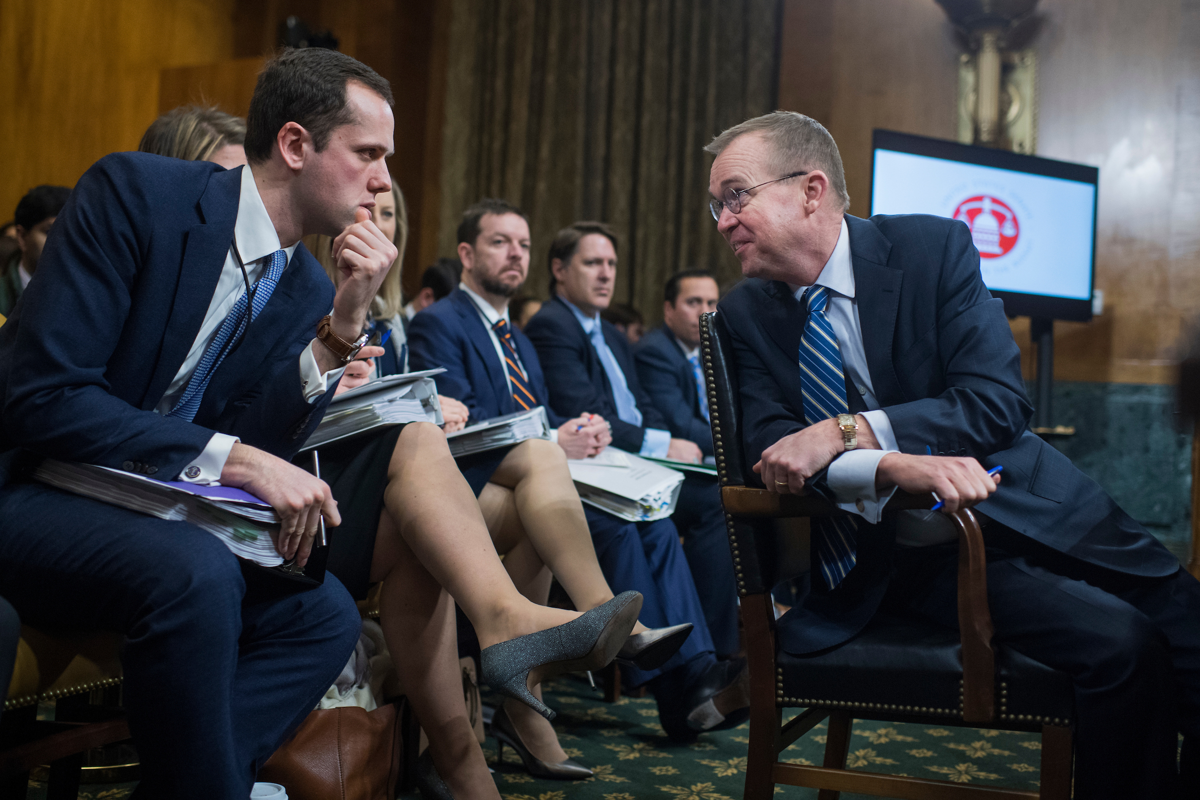 "Mick Mulvaney, right, director of the Office of Management and Budget, talks with aide Jonny Slemrod during a Senate Budget Committee hearing on the ""President's Fiscal Year 2019 Budget"" in Dirksen Building on February 13, 2018. (Photo By Tom Williams/CQ Roll Call)"