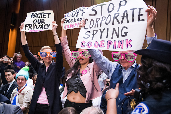 UNITED STATES - APRIL 10: Protesters hold signs before Facebook CEO Mark Zuckerberg testified before a joint hearing of the Senate Judiciary and Commerce Committees on the protection of user data in Hart Building on April 10, 2018. (Photo By Tom Williams/CQ Roll Call)