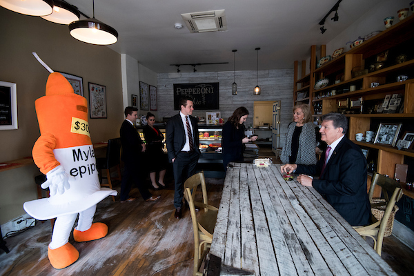 UNITED STATES - APRIL 11: Sen. Joe Manchin, D-W. Va., tries the olives as a man from the NRSC dressed as a epipen looks on at the Pepperoni Chic pop up restaurant in Washington on Wednesday, April 11, 2018. Sen. Manchin and members of his staff stopped by the restaurant, owned by West Virginia native Karen Shannon, to dine on pepperoni rolls, a West Virginia delicacy. The National Republican Senate Committee send the costumed man to highlight a controversy involving Manchin's daughter, who is the CEO of Mylan, a manufacturer of epipens. (Photo By Bill Clark/CQ Roll Call)