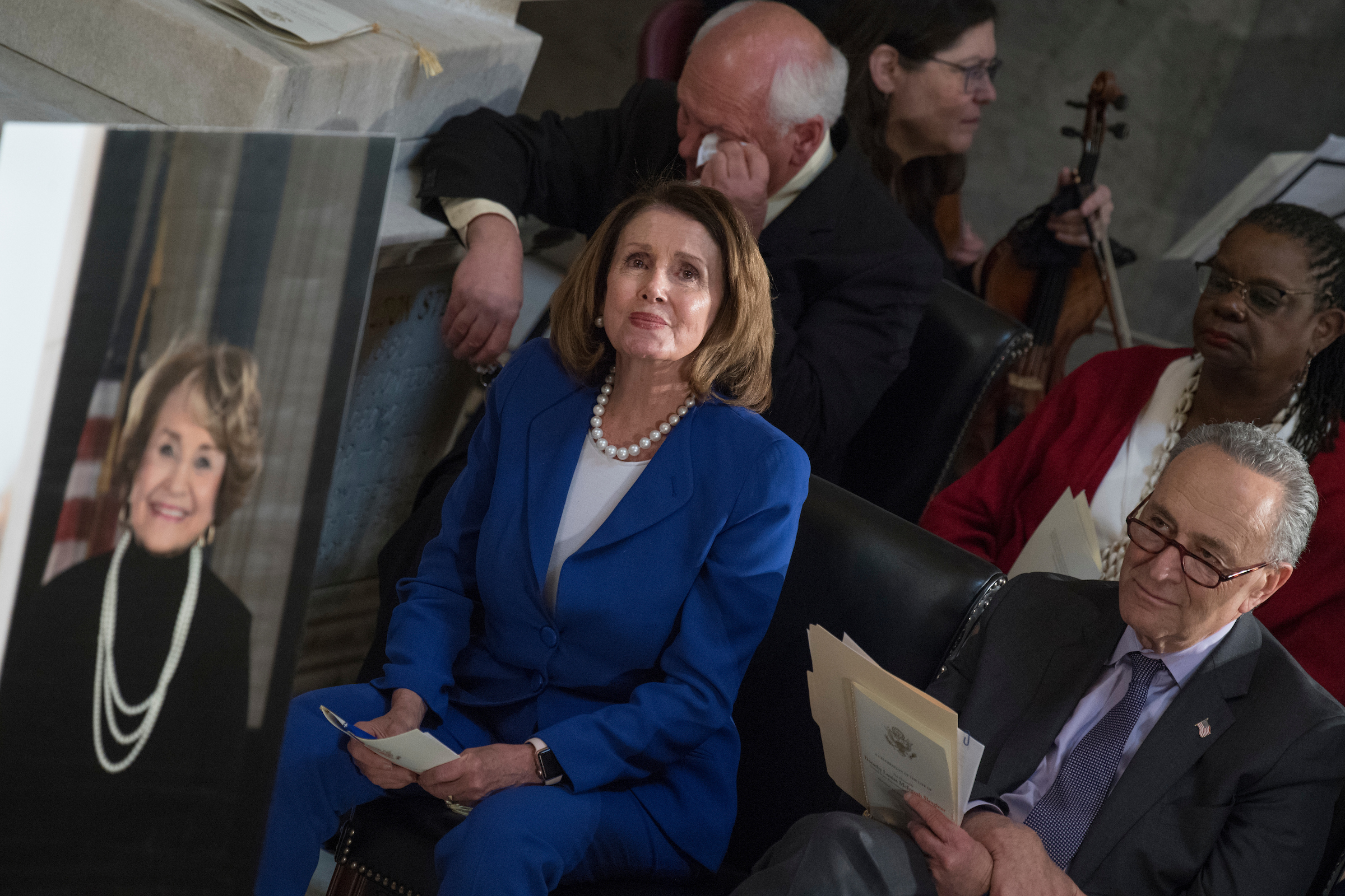 "House Minority Leader Nancy Pelosi, D-Calif., center, Senate Minority Leader Charles Schumer, D-N.Y., right, Reps. Gwen Moore, D-Wis., and Paul Tonko, D-N.Y., listen to rendition of ""Amazing Grace"" during a memorial service for the late Rep. Louise Slaughter, D-N.Y., in the Capitol's Statuary Hall on April 18, 2018. Slaughter, pictured at left, passed away on March 16, 2018, at age 88. (Photo By Tom Williams/CQ Roll Call)"