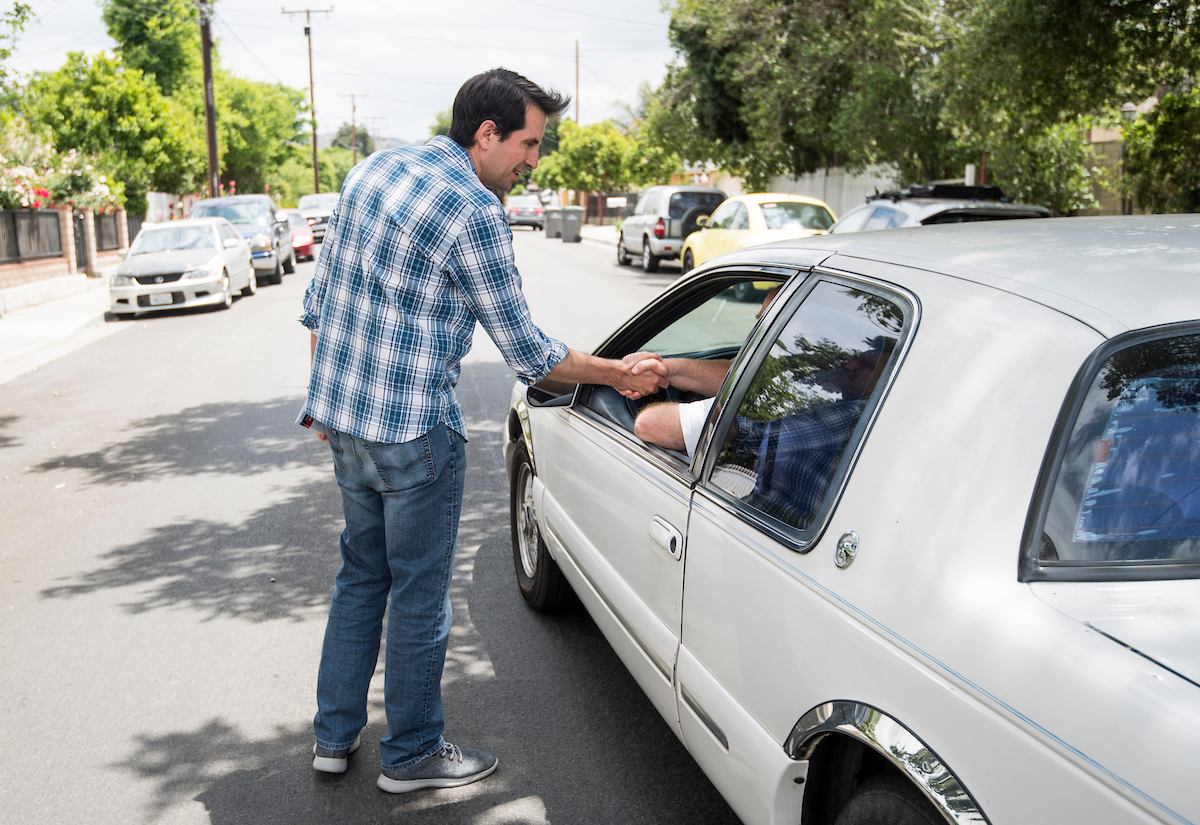 yan Caforio, Democrat running for California's 25th Congressional district seat in Congress, shakes hands with the driver of a passing car. (Bill Clark/CQ Roll Call).
