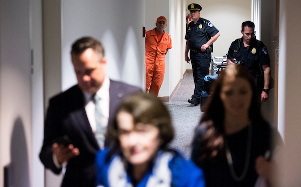 "UNITED STATES - MAY 9: CodePink protester Tighe Barry, under arrest, yells ""no torture"" as Sen. Dianne Feinstein, D-Calif., arrives via a back hallway for the Senate (Select) Intelligence Committee confirmation hearing for Gina Haspel, nominee to be director of the Central Intelligence Agency, on Wednesday, May 9, 2018. Several protesters were arrested in the hearing room before the start of the hearing. (Photo By Bill Clark/CQ Roll Call)"