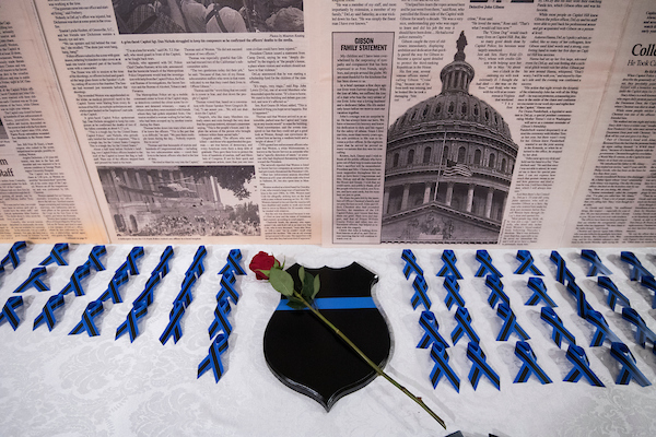 UNITED STATES - MAY 8: Blue ribbons, a rose, and a copy of Roll Call's coverage of the July 24, 1998 shooting were on display at the annual United States Capitol Police memorial service on Tuesday, May 8, 2018, honoring the four USCP officers who have died in the line of duty. This year is the 20th anniversary of the deaths of Officer Jacob Chestnut and Detective John Gibson while protecting the U.S. Capitol from a gunman's attack on July 24, 1998. (Photo By Bill Clark/CQ Roll Call)