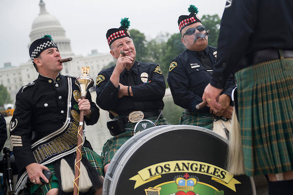 "UNITED STATES - MAY 14: From left, Drum Major Ken Misch, Drum Sgt. Charlie Ezelle, and Roberto ""Boom Boom"" Lopez, of the Los Angeles Police Emerald Society Pipes and Drums, smoke cigars near the Capitol Reflecting Pool after participating in a competition that was part of National Police Week on May 14, 2018. (Photo By Tom Williams/CQ Roll Call)"